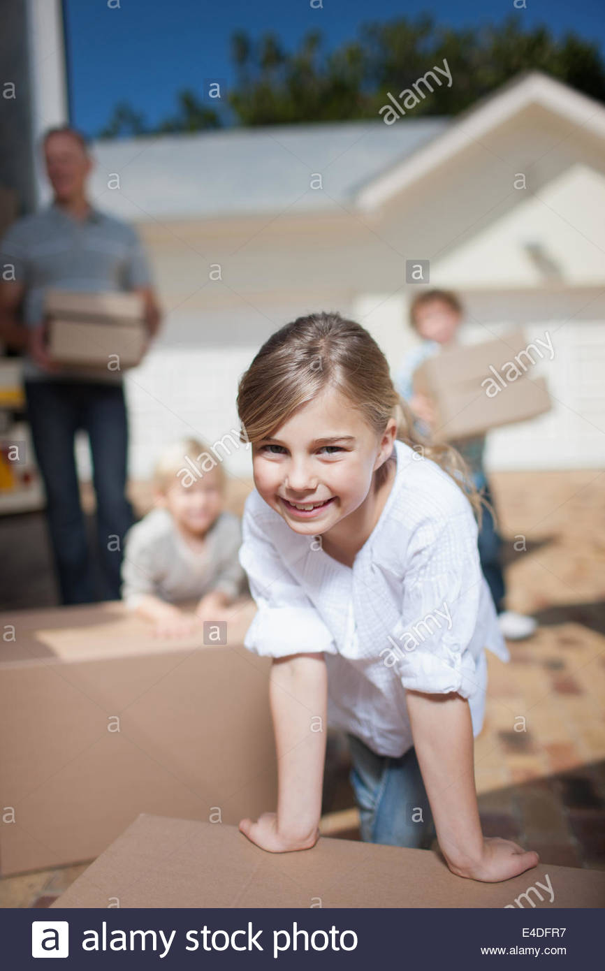 Family unloading boxes from moving van - Stock Image