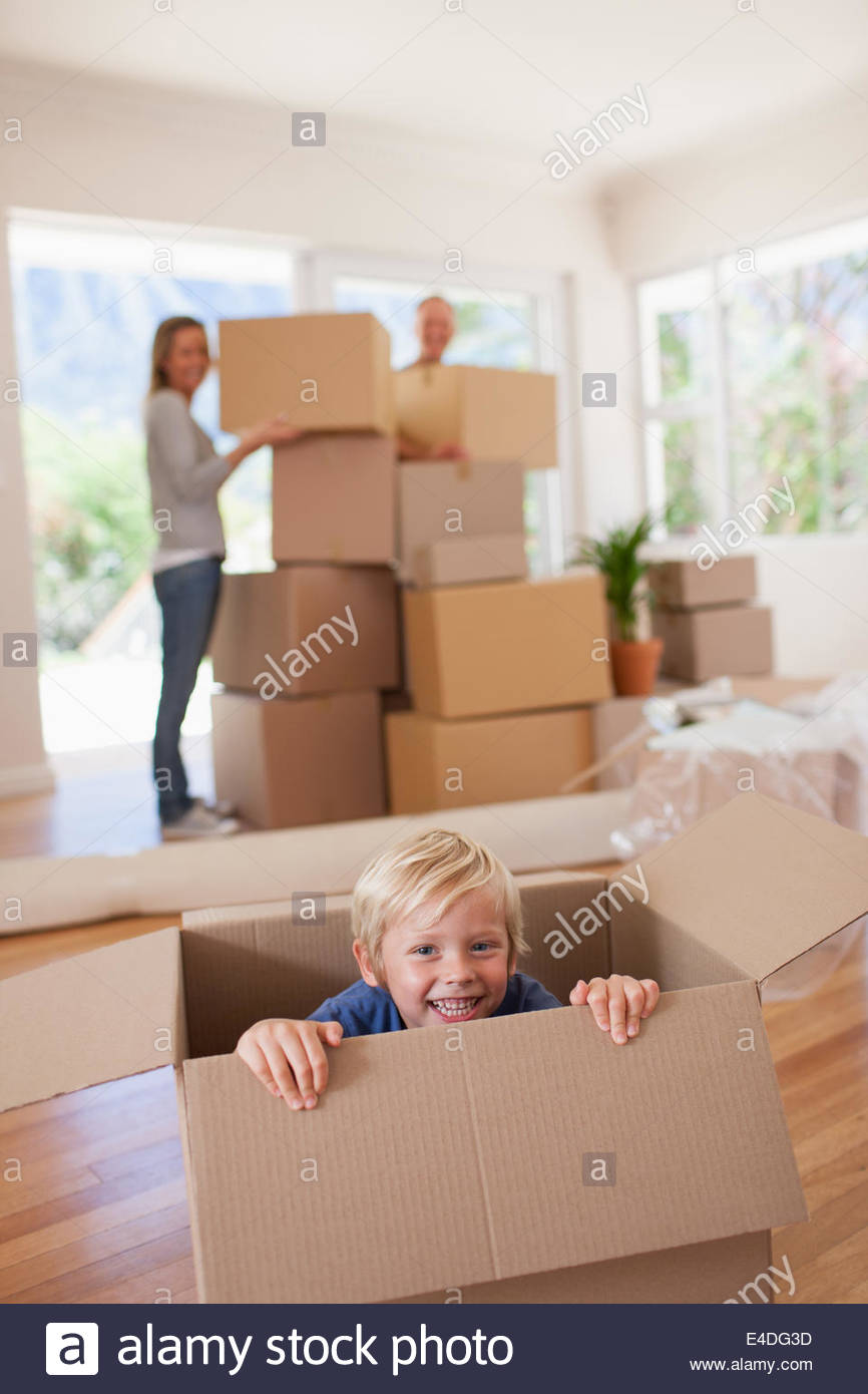 Smiling boy playing on box in new house - Stock Image