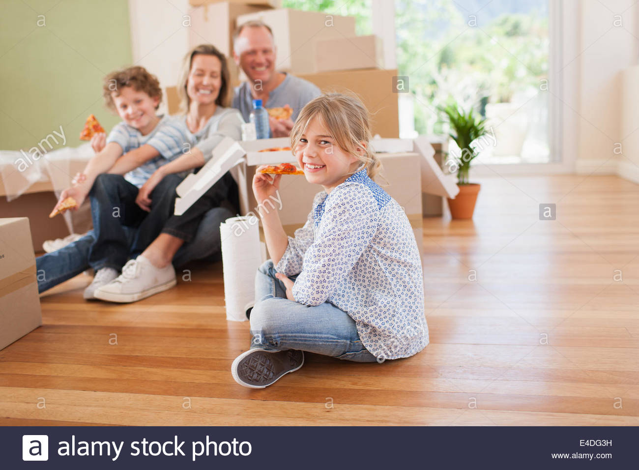 Family eating pizza on the floor in their new house - Stock Image
