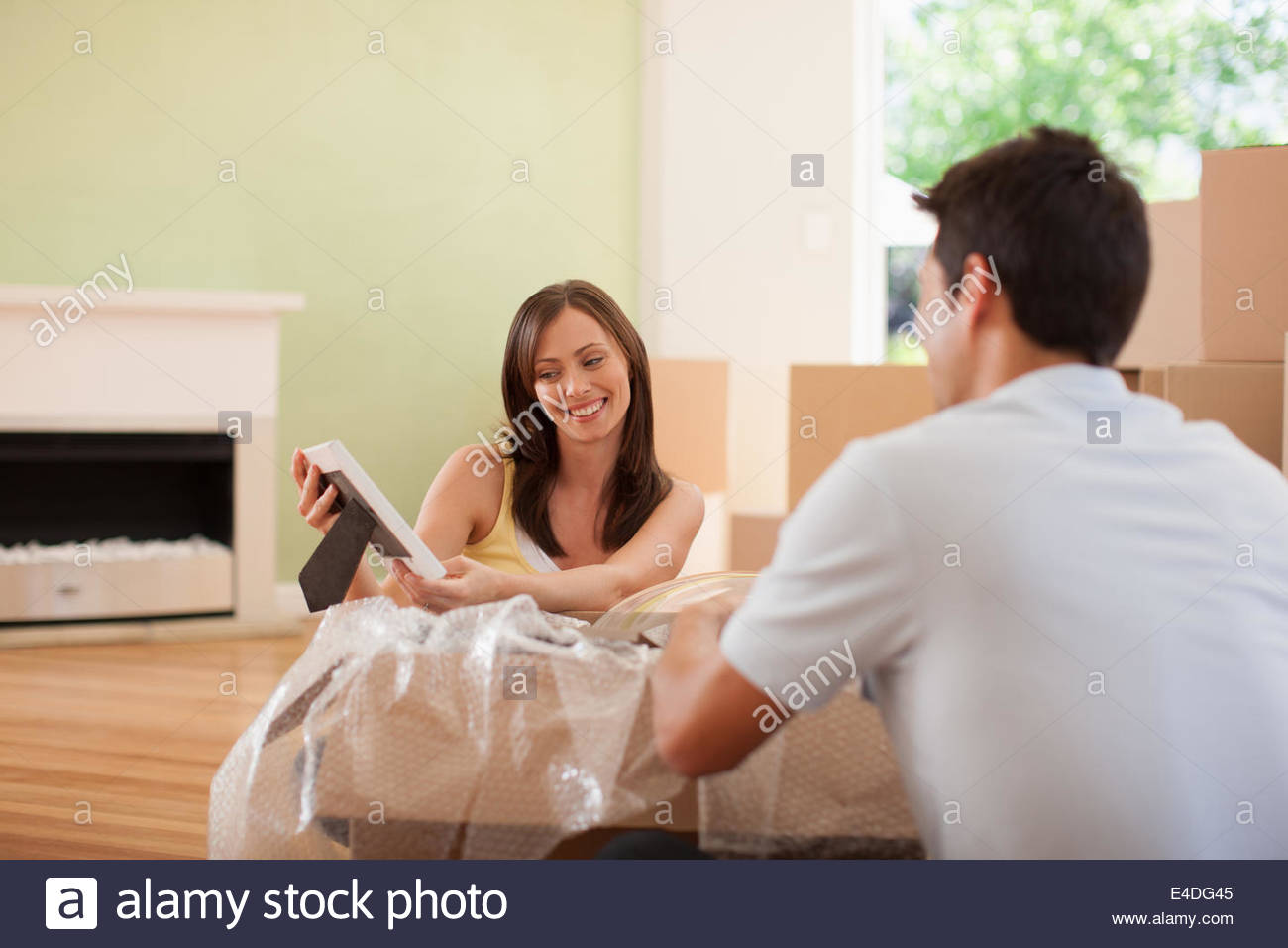 Couple unpacking pictures in new house - Stock Image