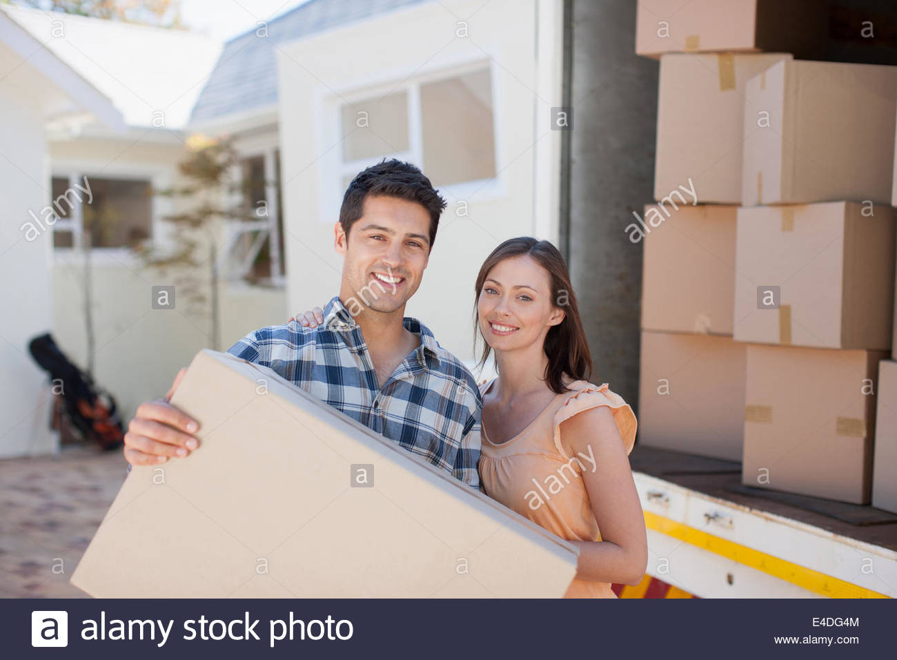 Couple carrying box from moving van - Stock Image