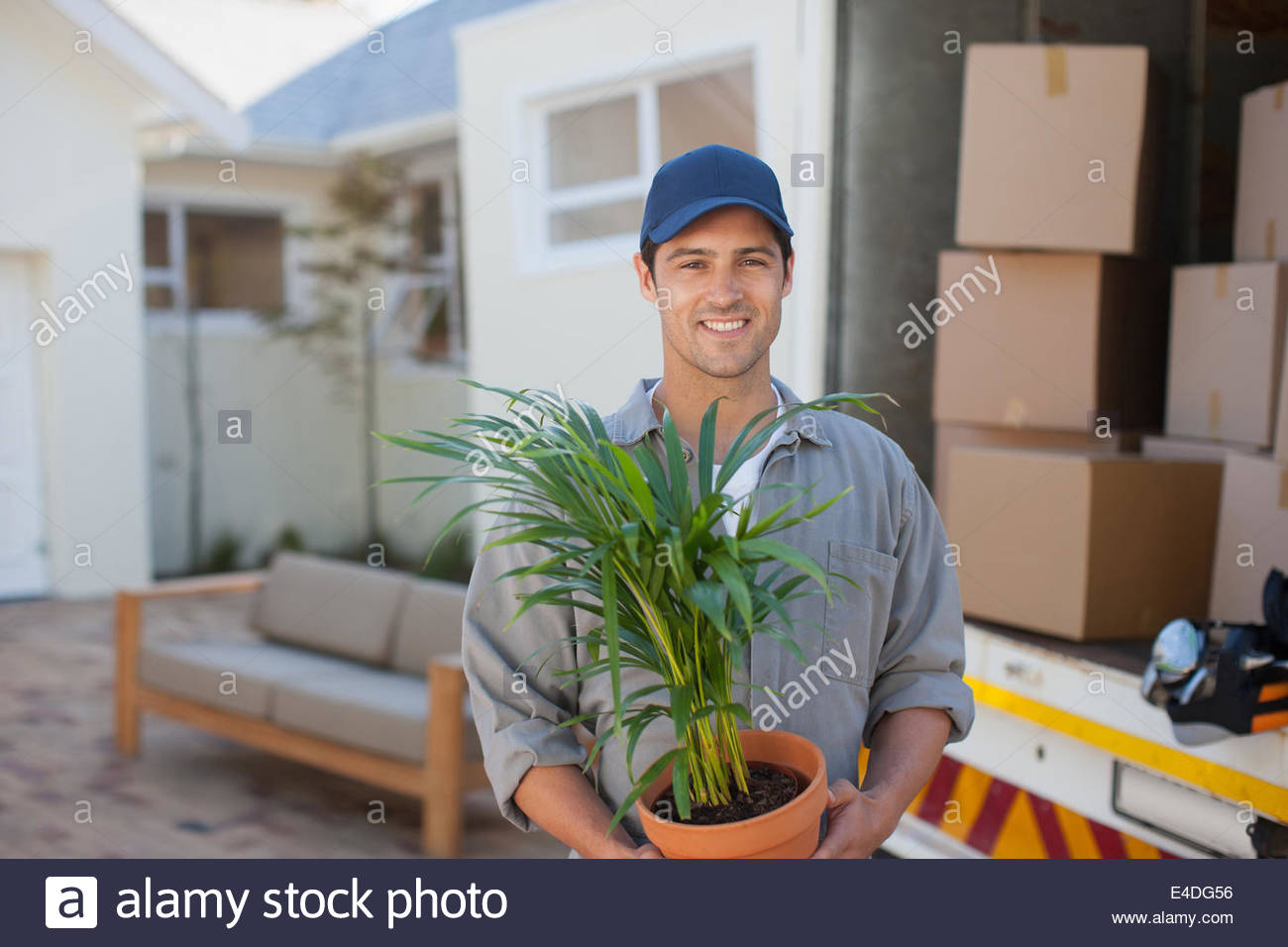 Smiling man carrying Flowerpot moving van - Stock Image