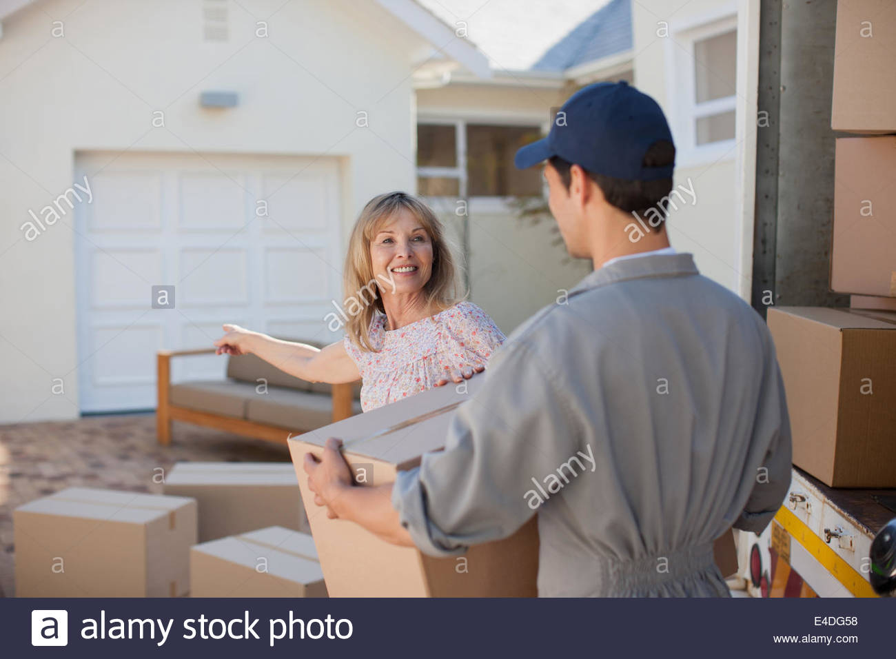 Mover helping woman move into new home - Stock Image