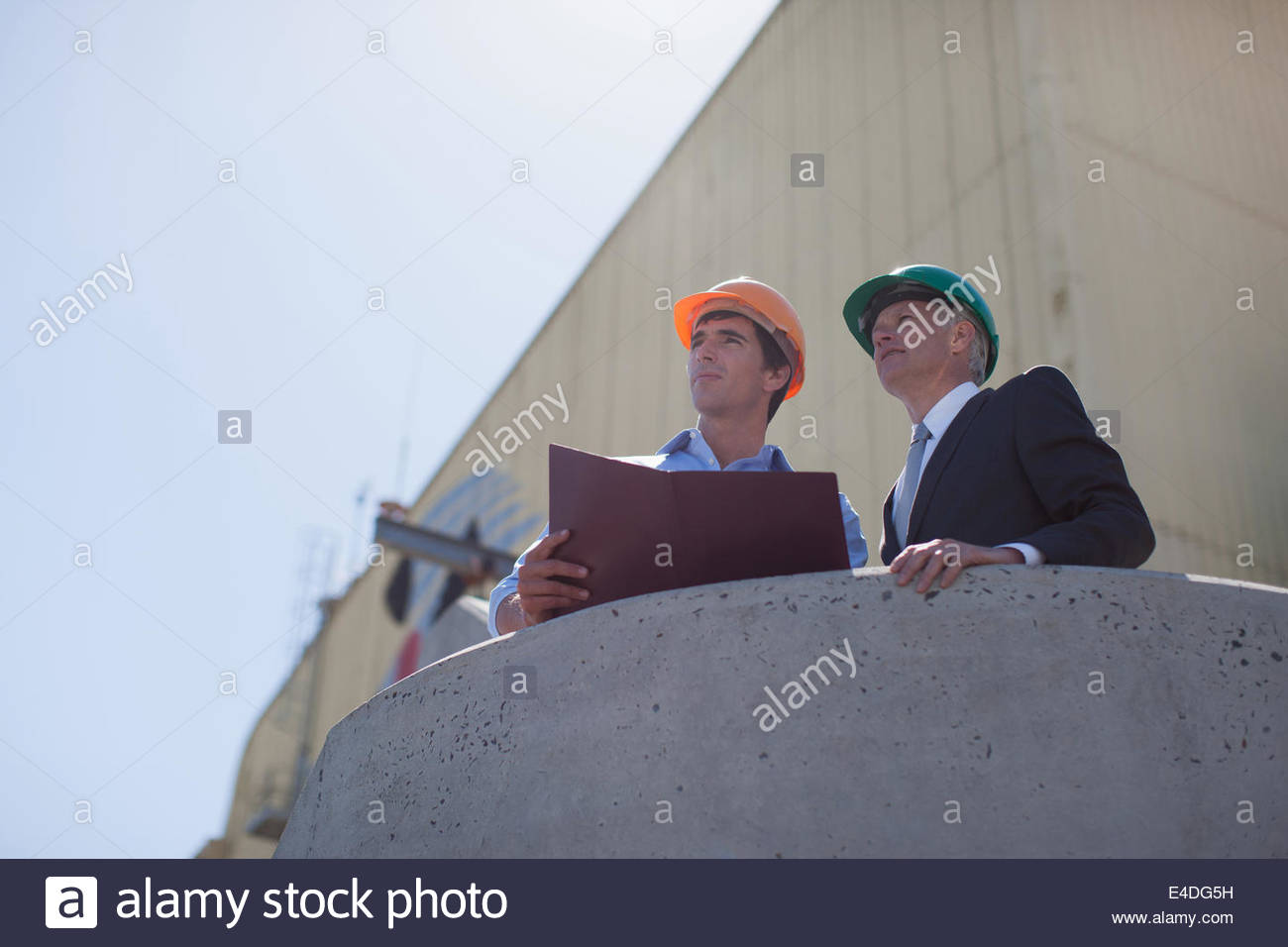 Businessman and worker in hard-hats outdoors - Stock Image