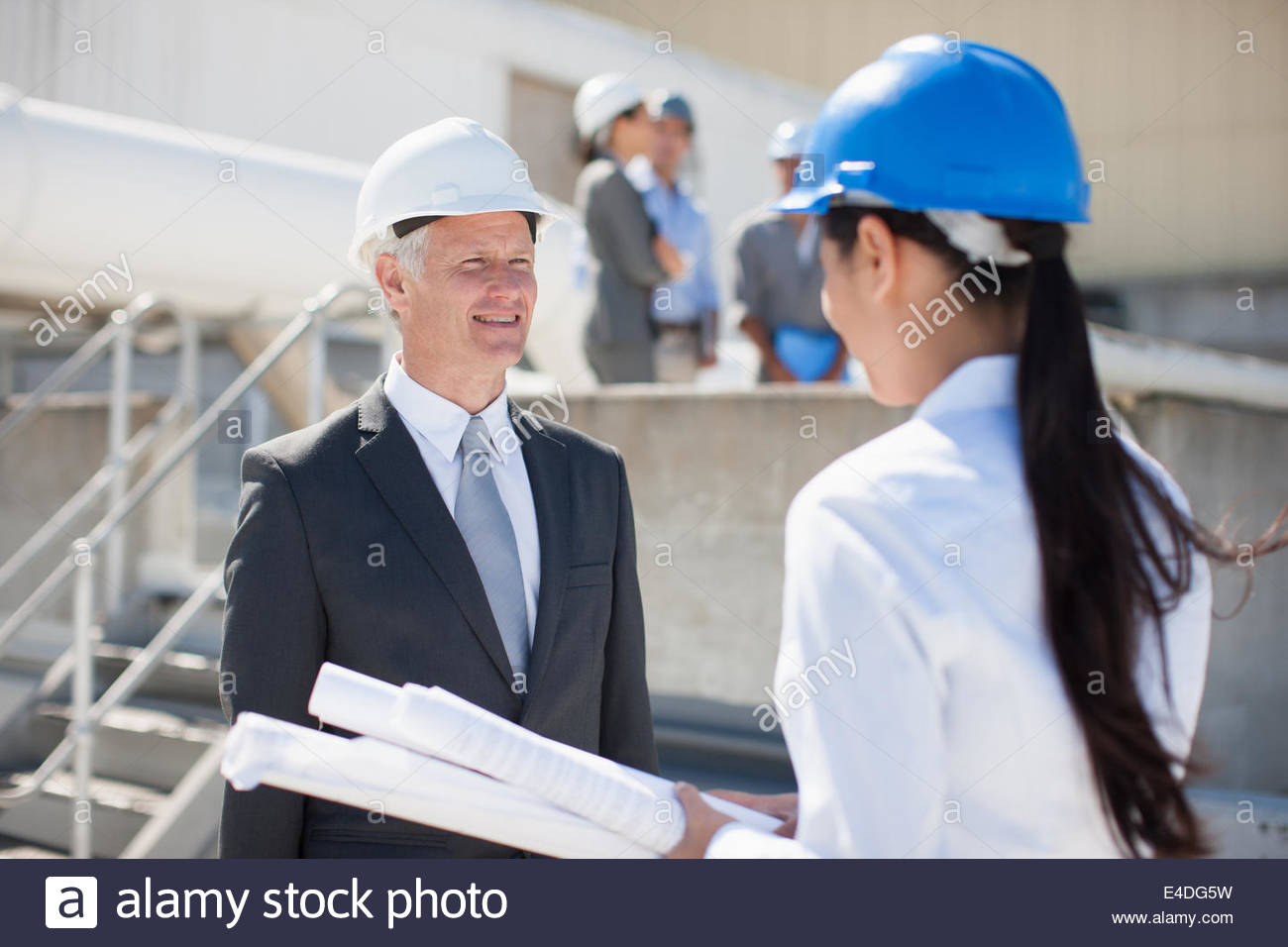 Businesswoman holding blueprints standing with co-workers - Stock Image
