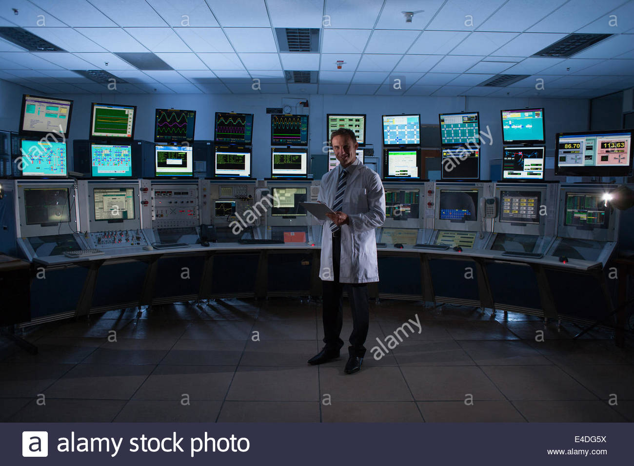 Scientist monitoring computers in control room - Stock Image