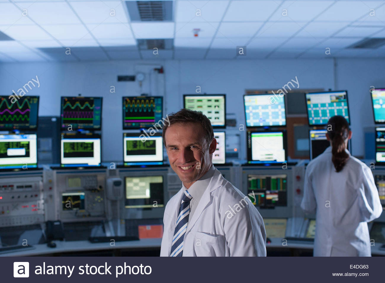 Scientists monitoring computers in control room - Stock Image