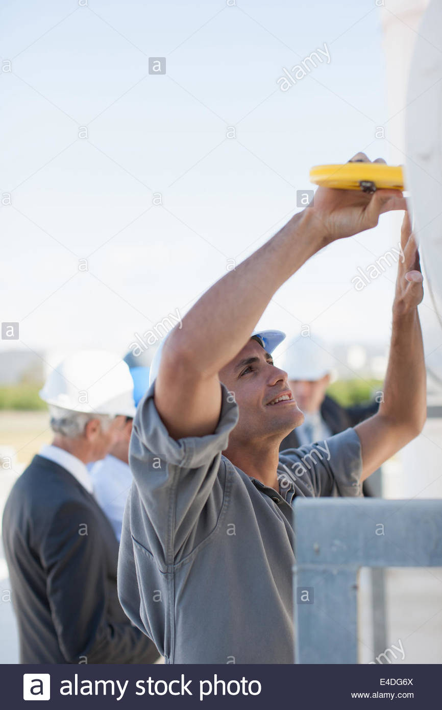 Worker measuring large pipe outdoors - Stock Image
