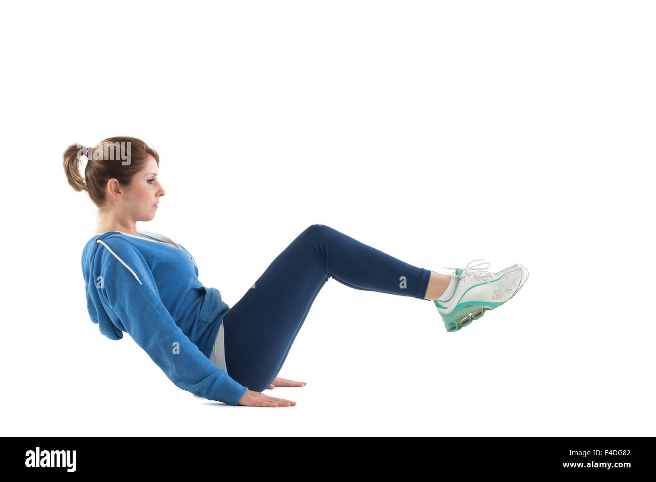 Side view of woman in core balance pilates pose - Stock Image