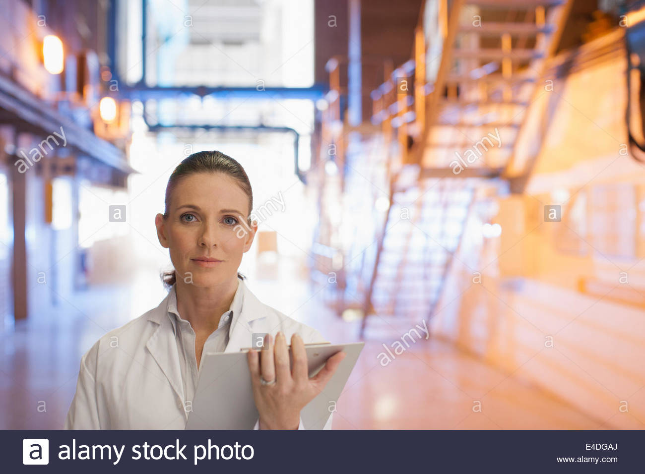 Scientist standing with clipboard in factory - Stock Image