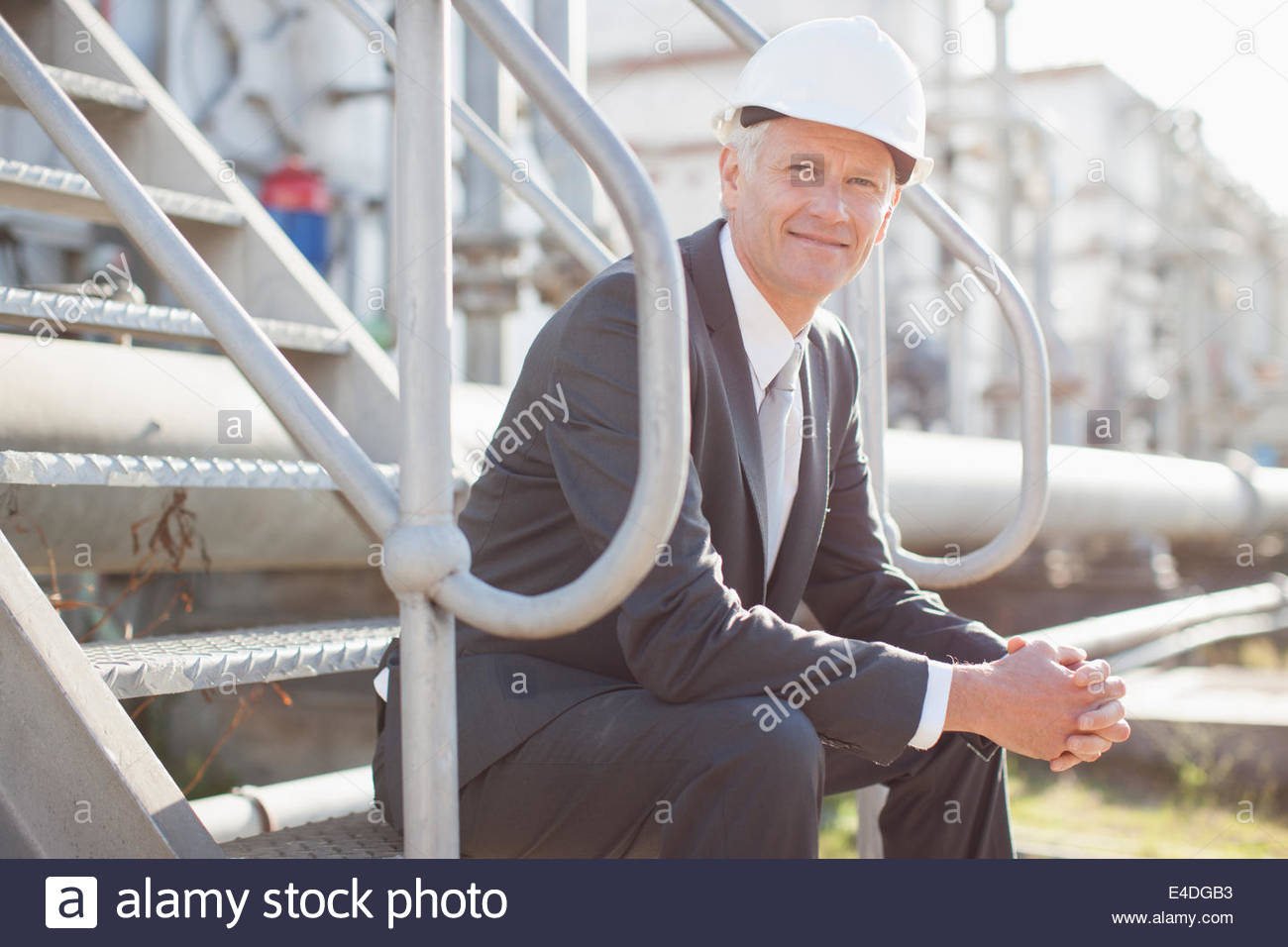 Businessman in hard-hat sitting on industrial steps - Stock Image