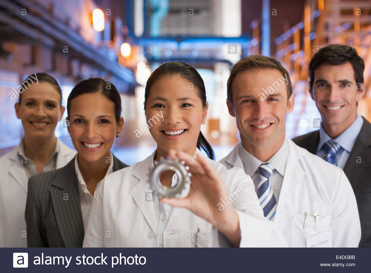 Business people looking at cog together - Stock Image