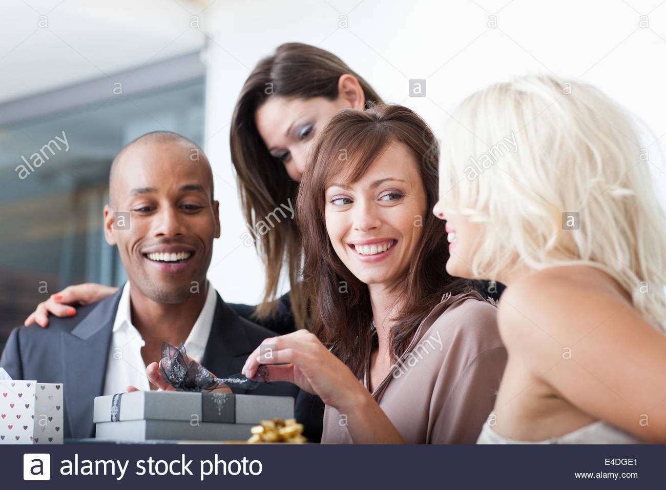Friends opening gifts - Stock Image