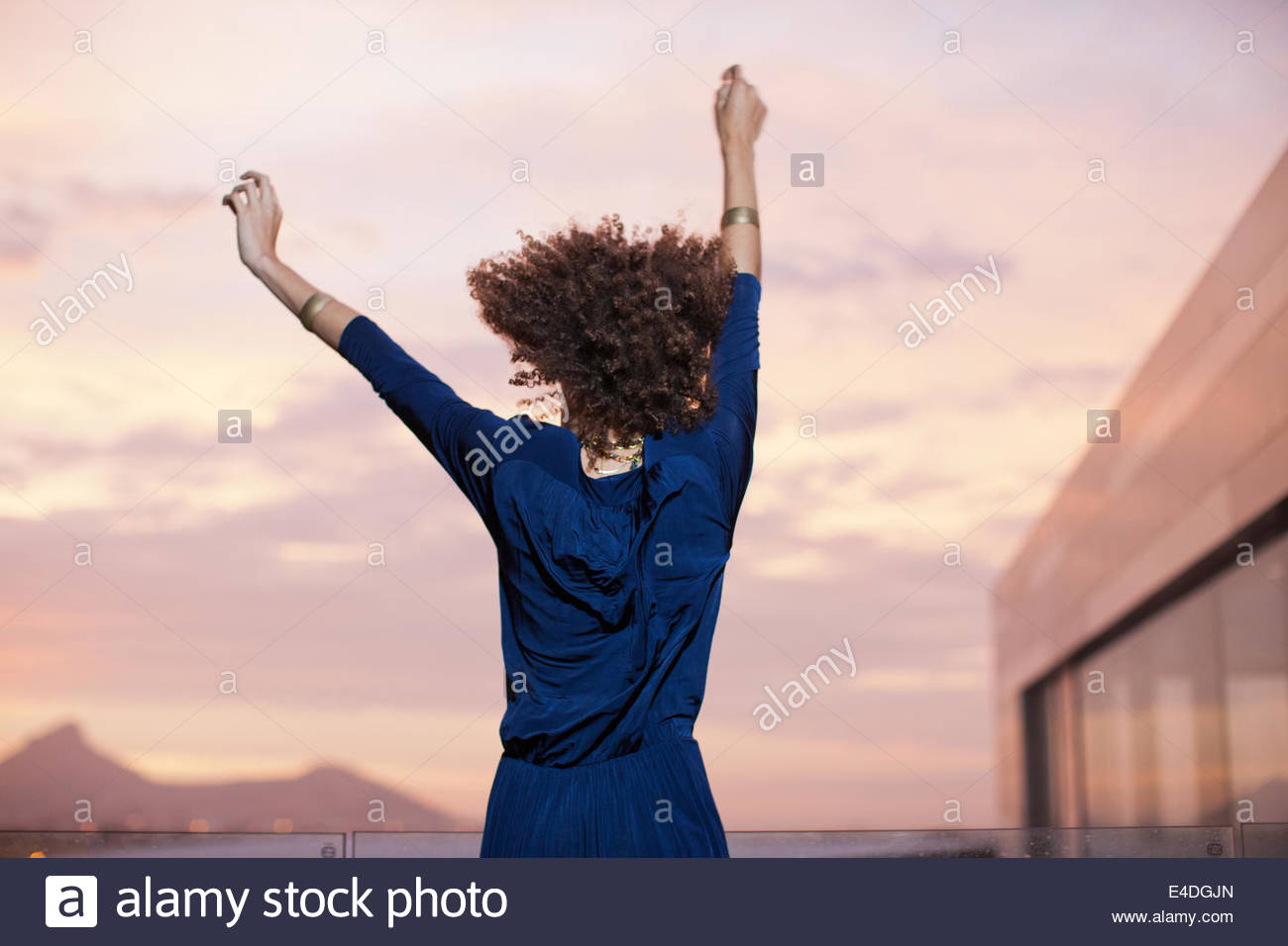 Woman dancing with arms raised - Stock Image