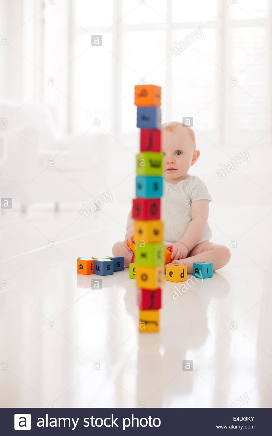 Baby on floor looking at stacked wood blocks - Stock Image