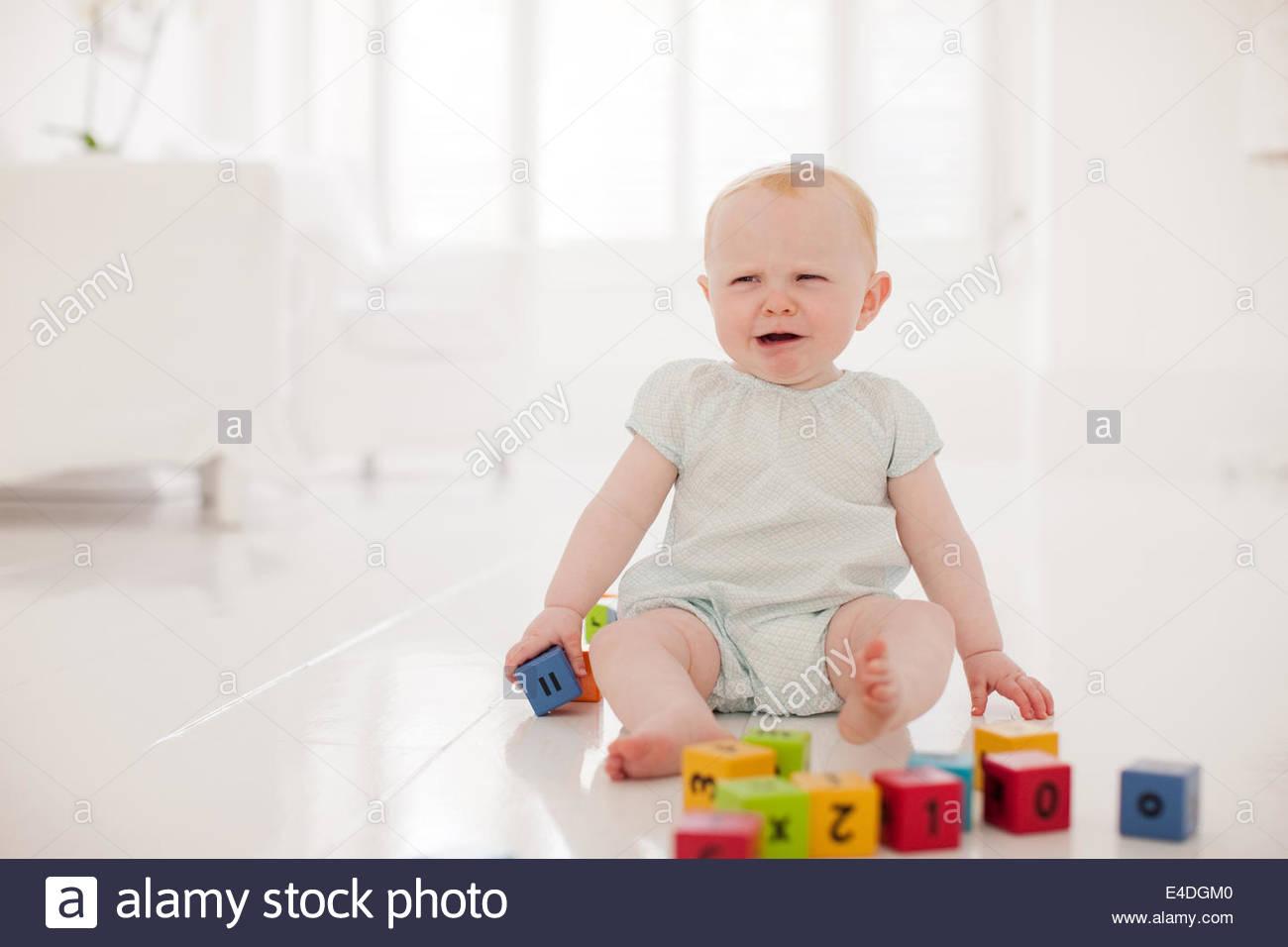 Baby  holding wood blocks and craying - Stock Image