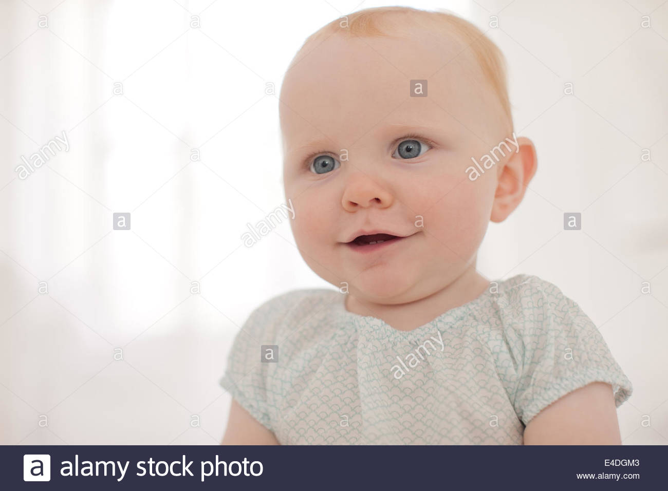 Smiling baby sitting on floor - Stock Image