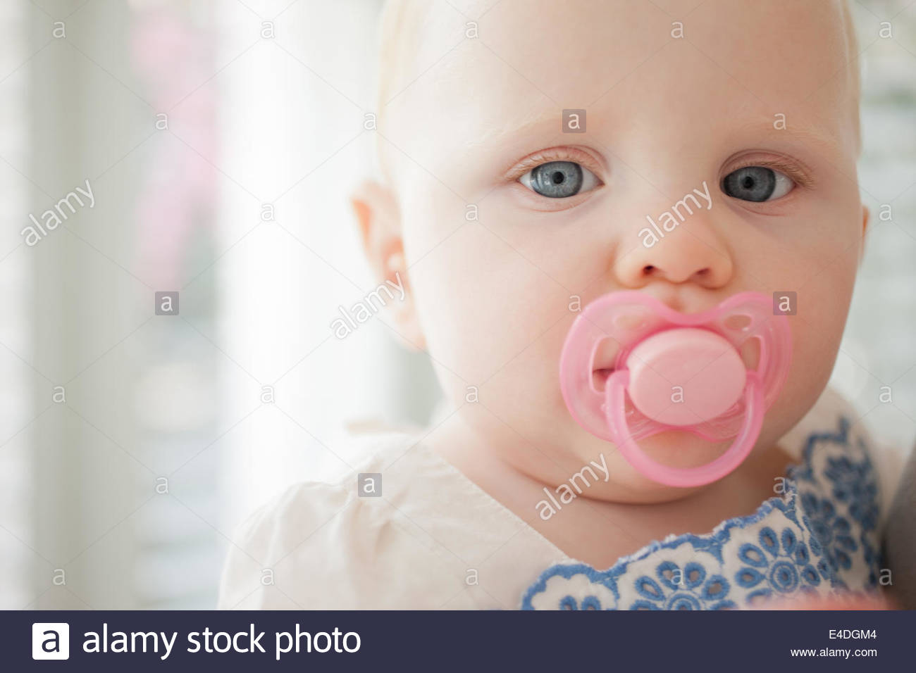 Close up of baby with pink pacifier - Stock Image