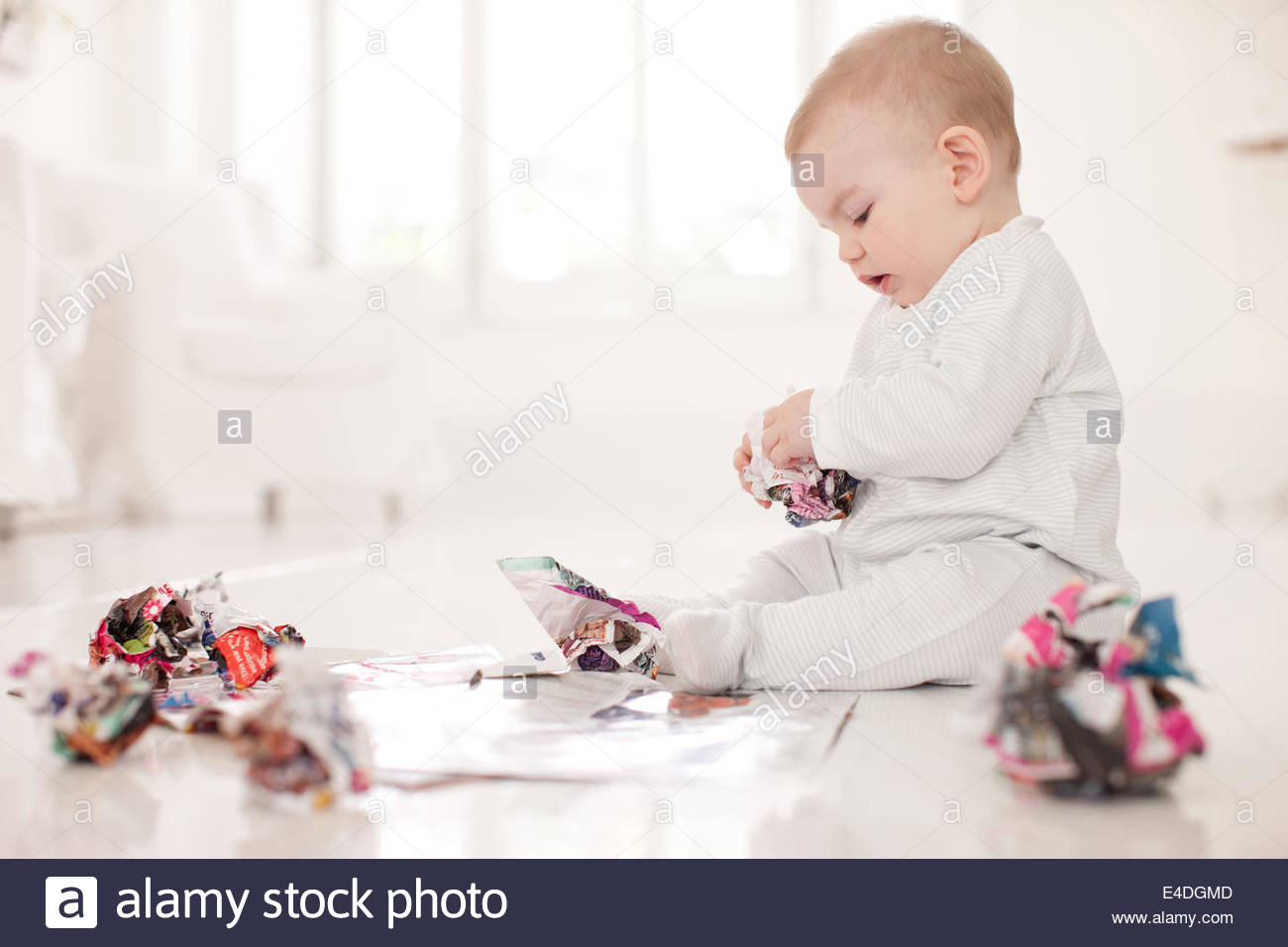 Baby on floor with crumpled paper - Stock Image