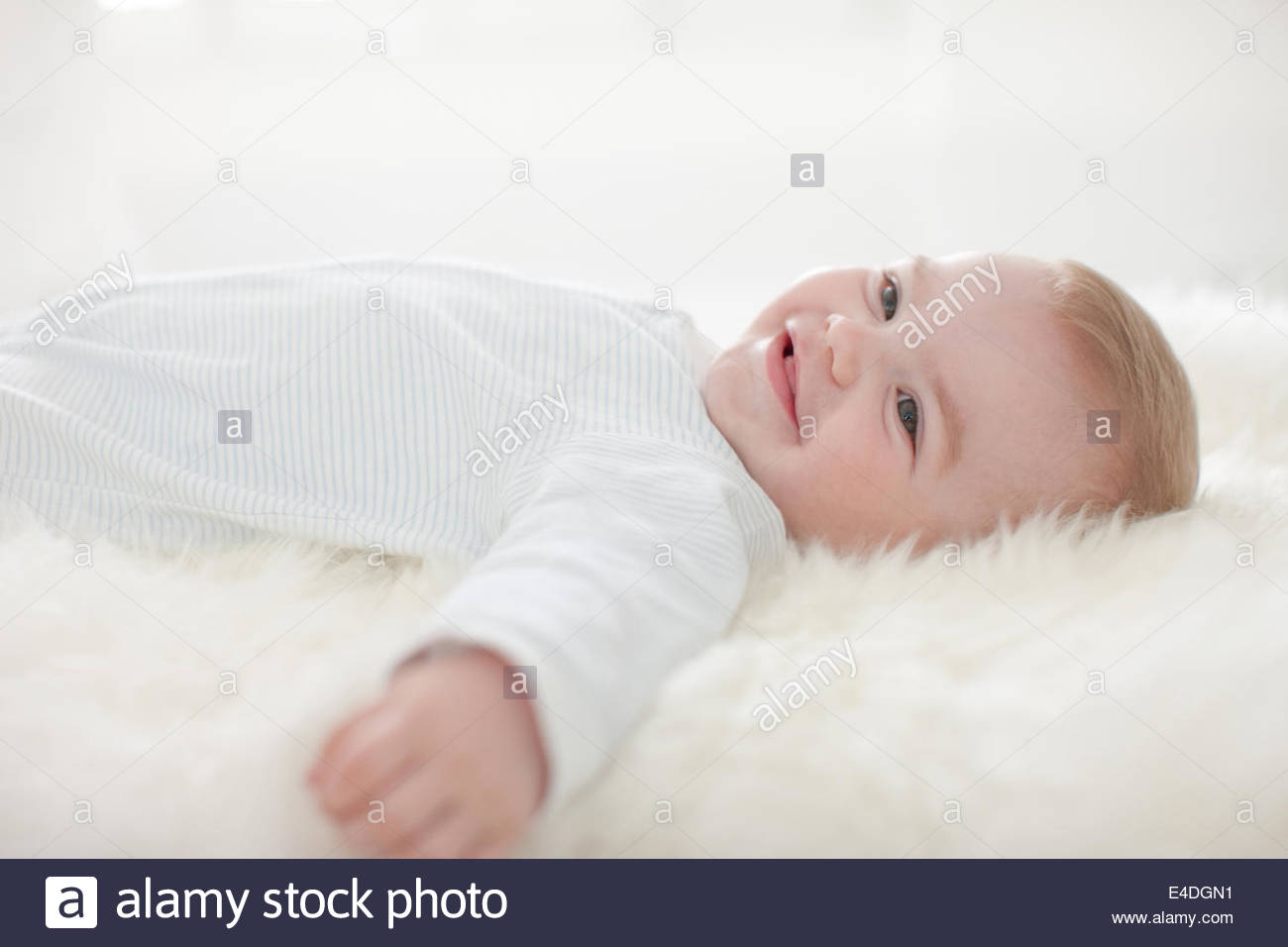 Smiling baby laying on rug - Stock Image