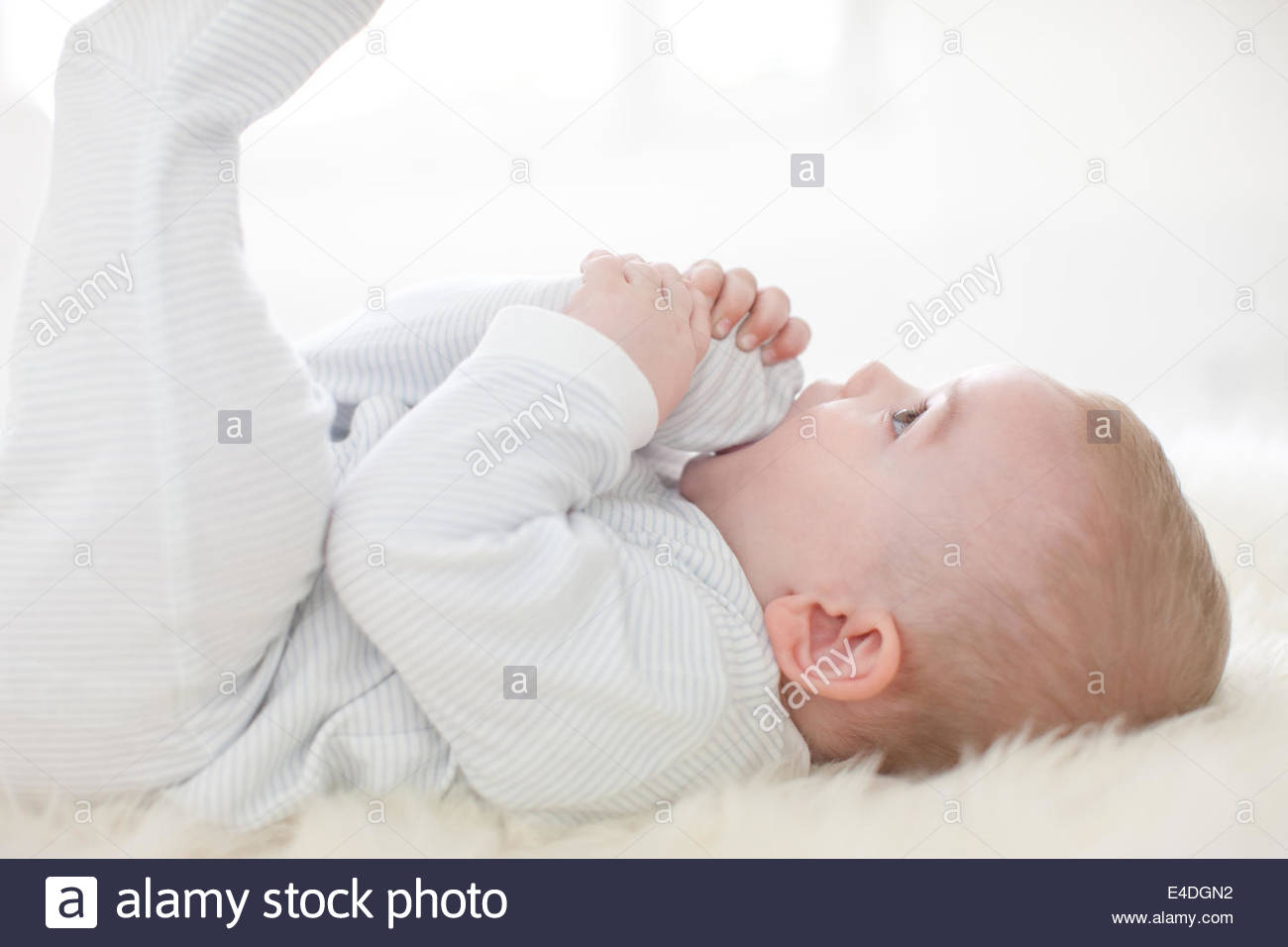 Close up of baby laying on rug - Stock Image