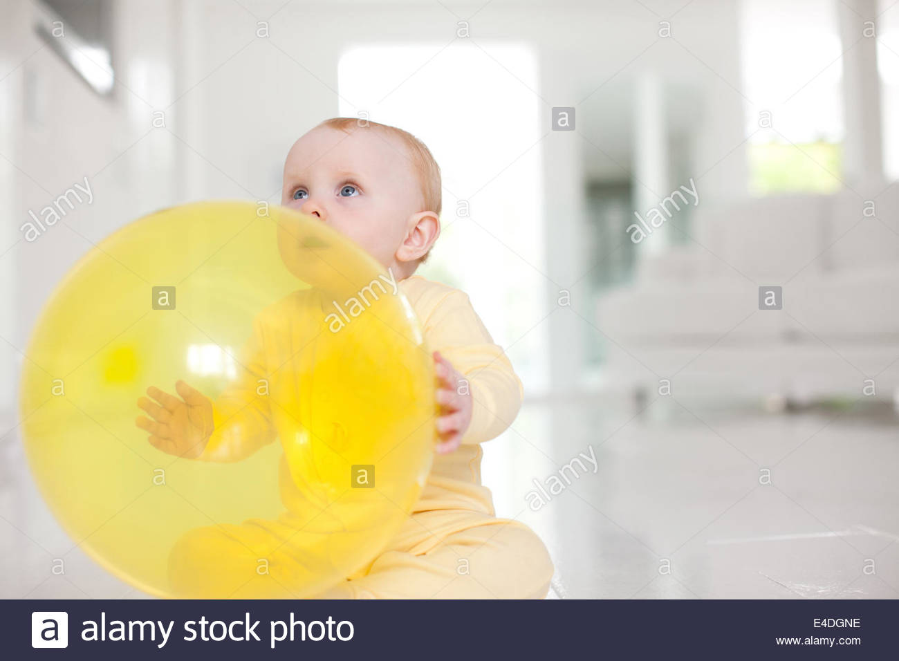 Curious baby with yellow balloon - Stock Image
