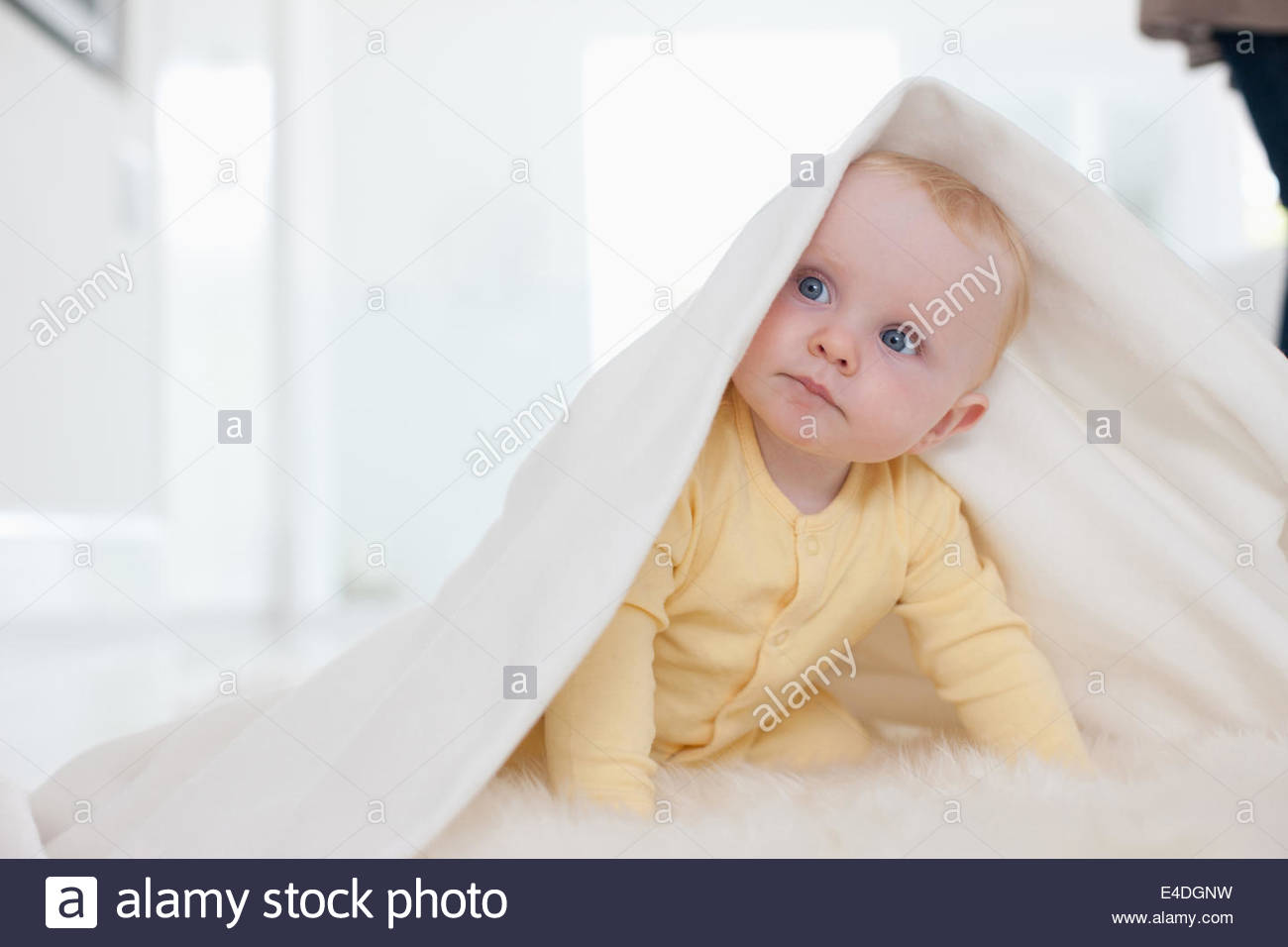 Baby playing with blanket on rug - Stock Image