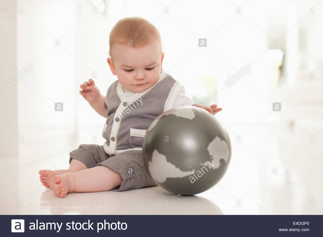 Smiling baby playing with globe on floor - Stock Image