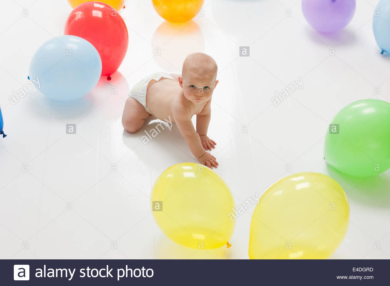 Baby reaching for balloons on floor Stock Photo