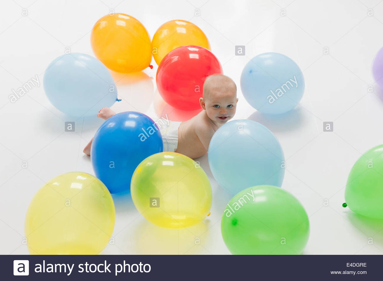 Baby laying on floor with balloons - Stock Image