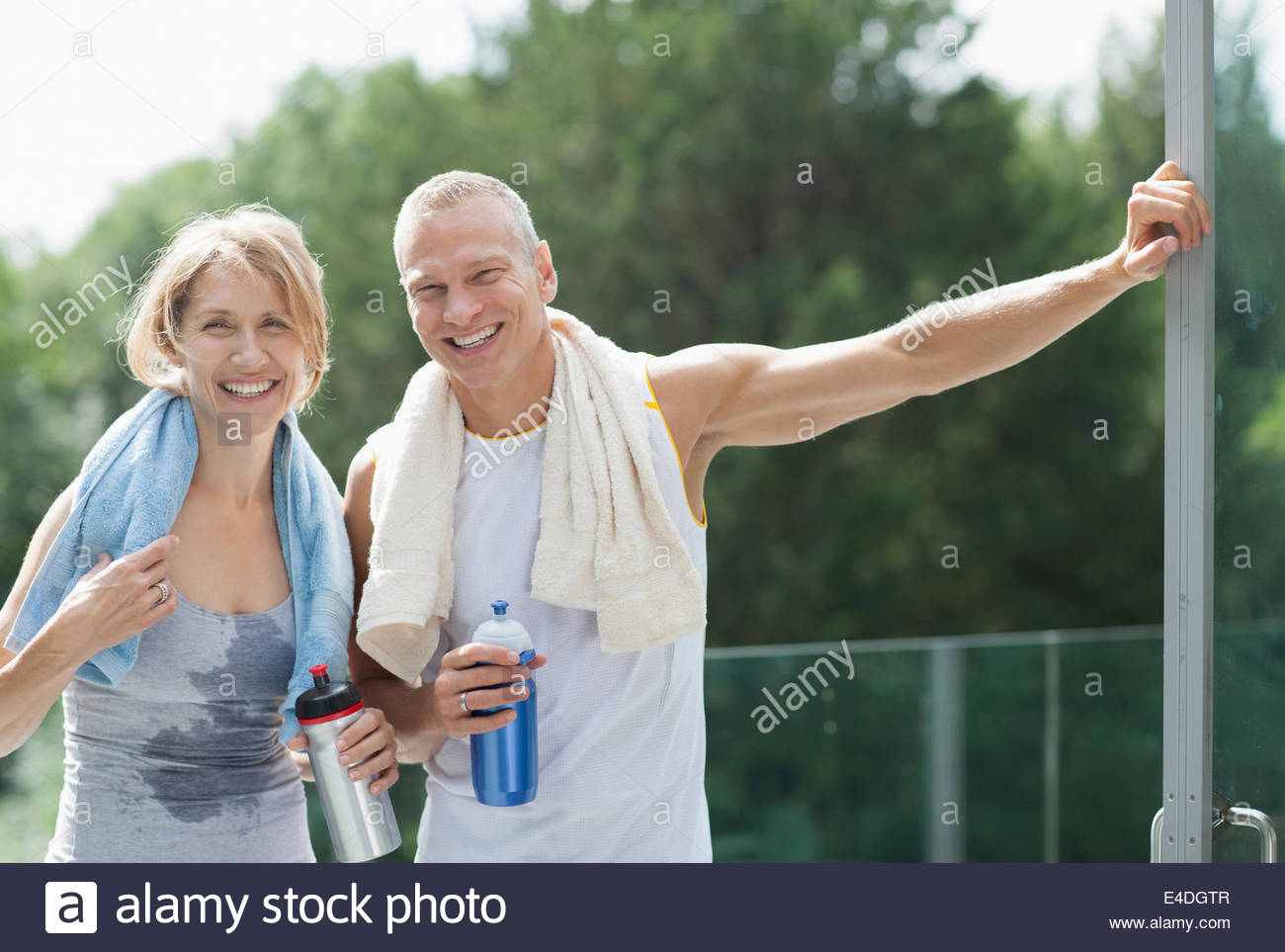 Smiling couple drinking water after exercise - Stock Image