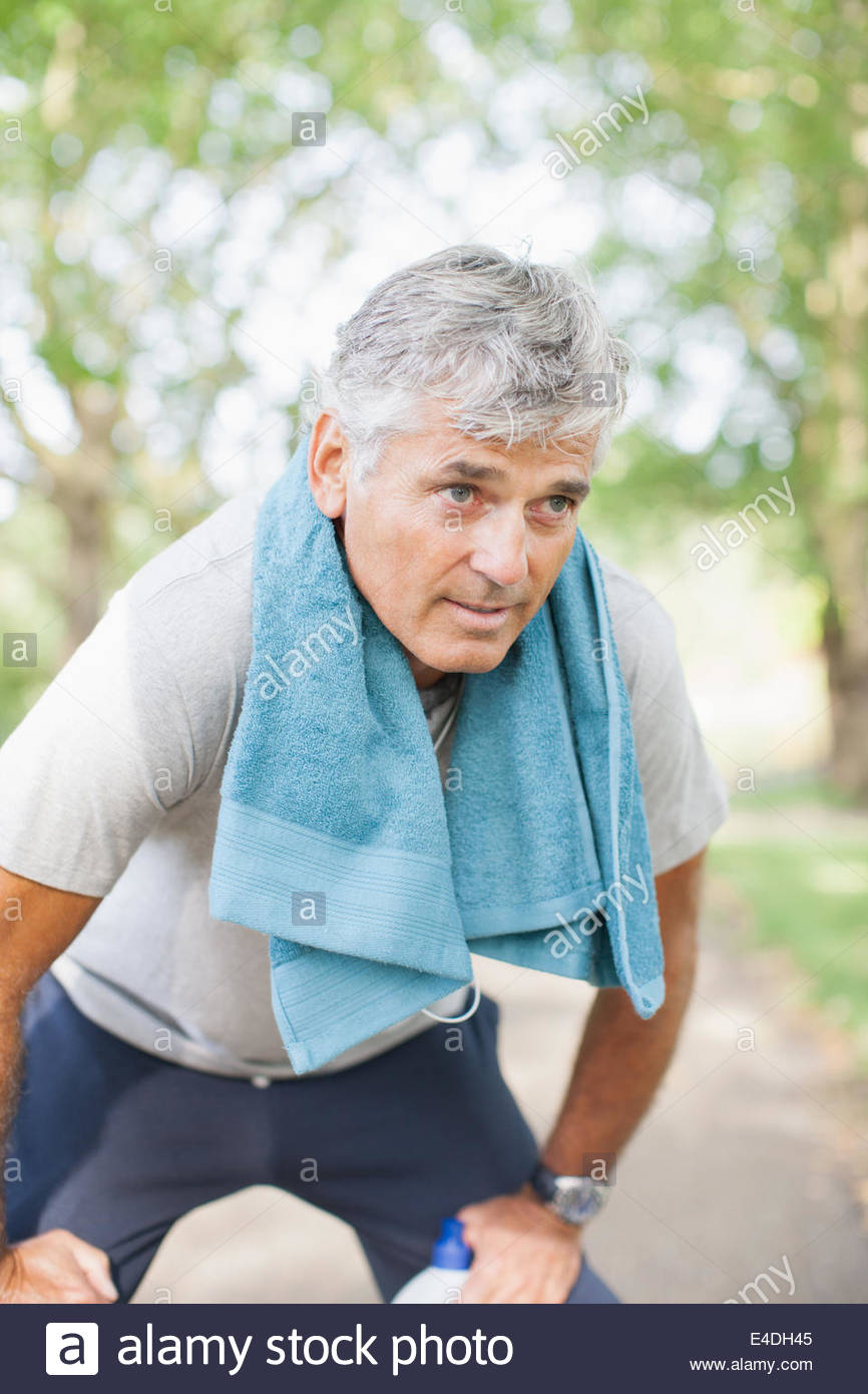 Serious man fatigued after exercise - Stock Image