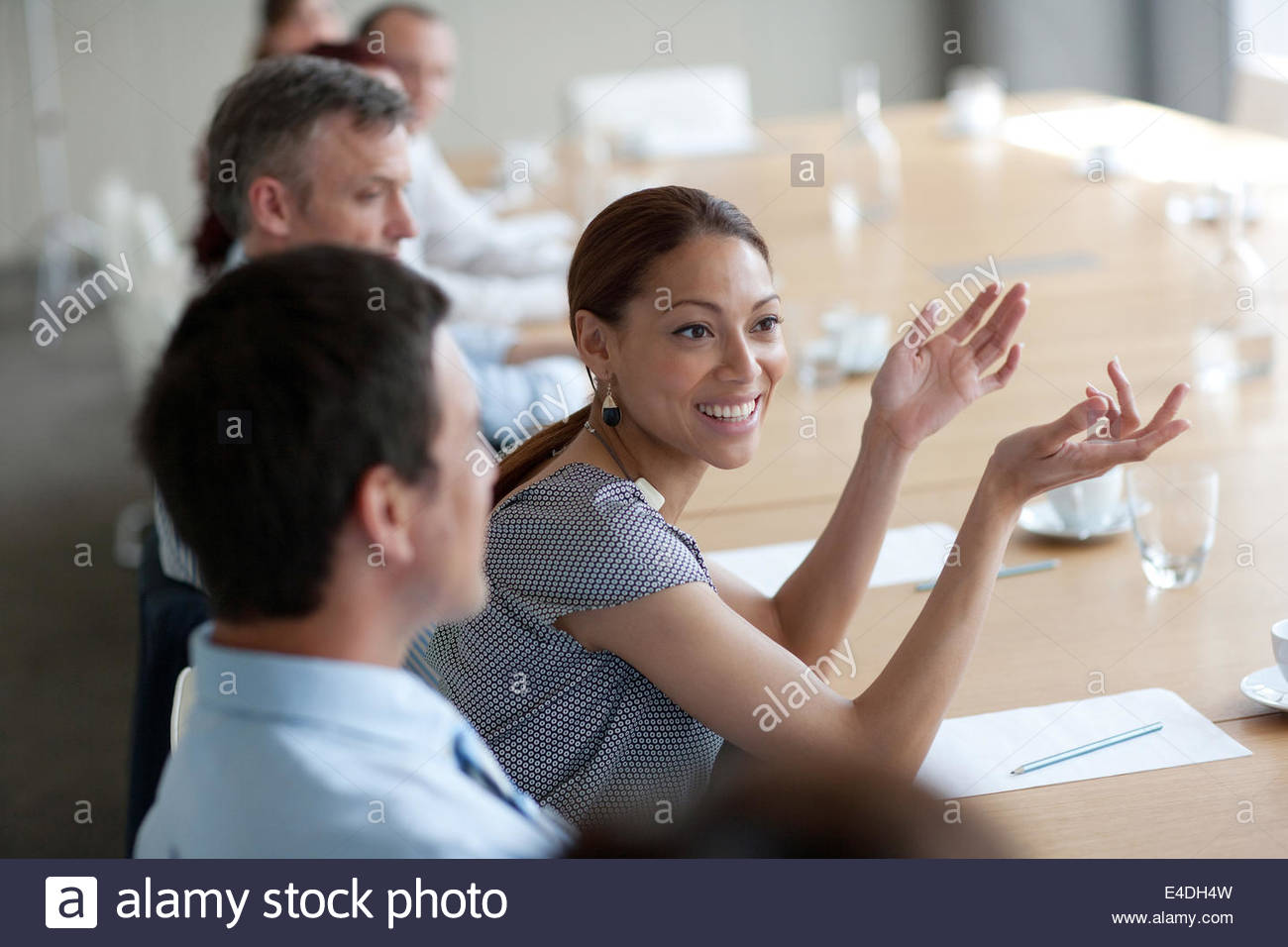 Smiling businesswoman gesturing in meeting in conference room - Stock Image