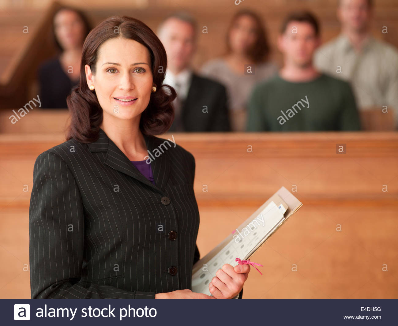 Smiling lawyer holding file in courtroom - Stock Image