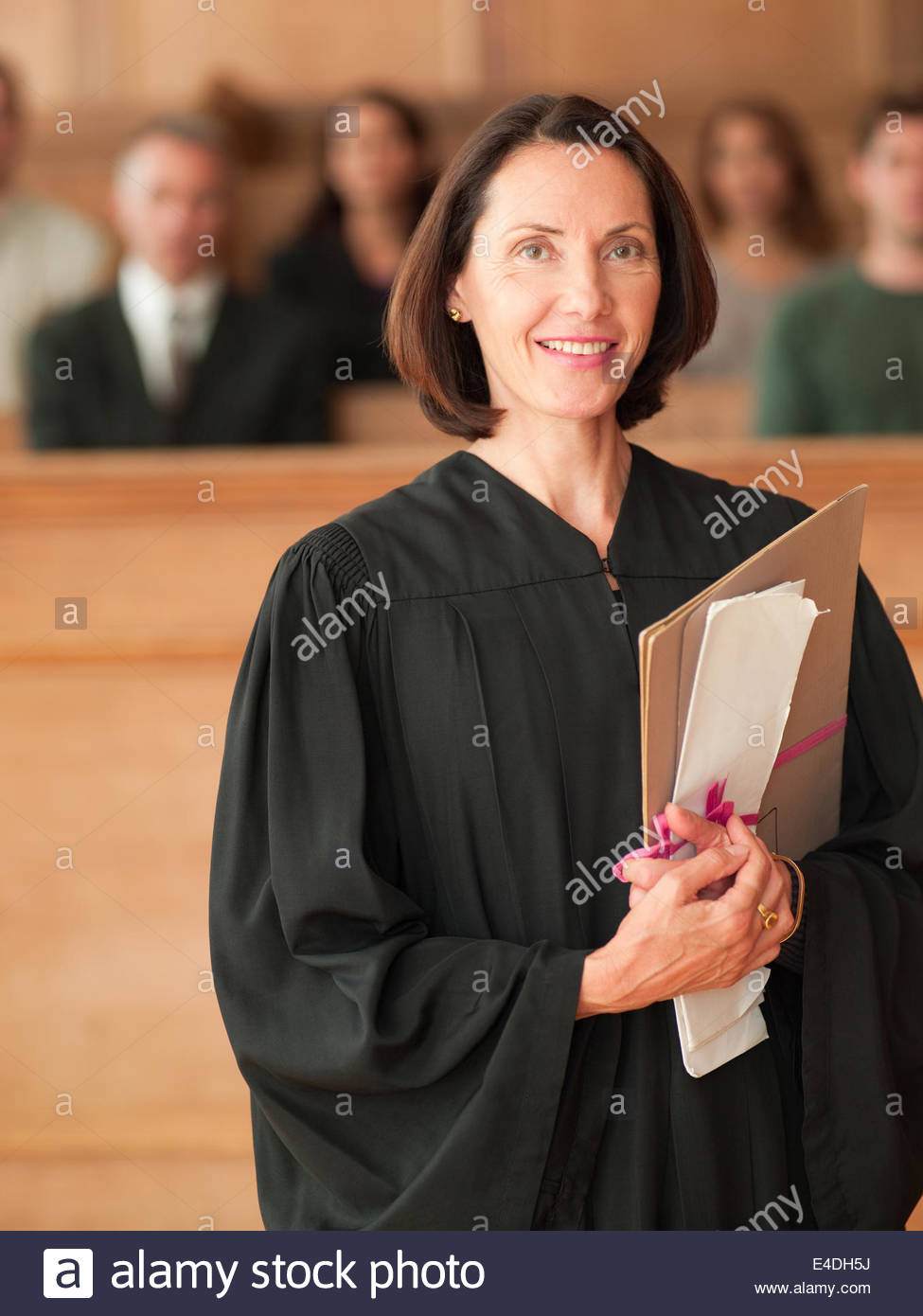Smiling judge holding file in courtroom - Stock Image