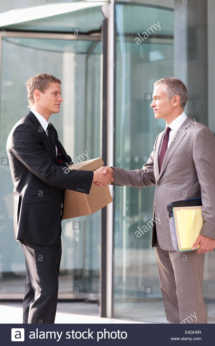 Lawyers shaking hands outside office building - Stock Image