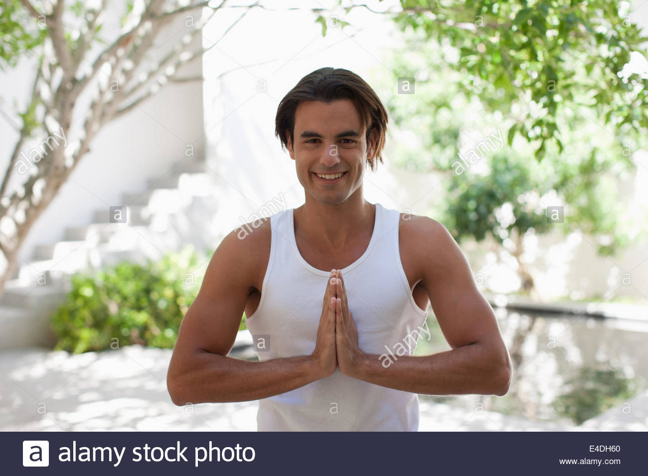 Man with eyes closed and hands clasped on patio - Stock Image