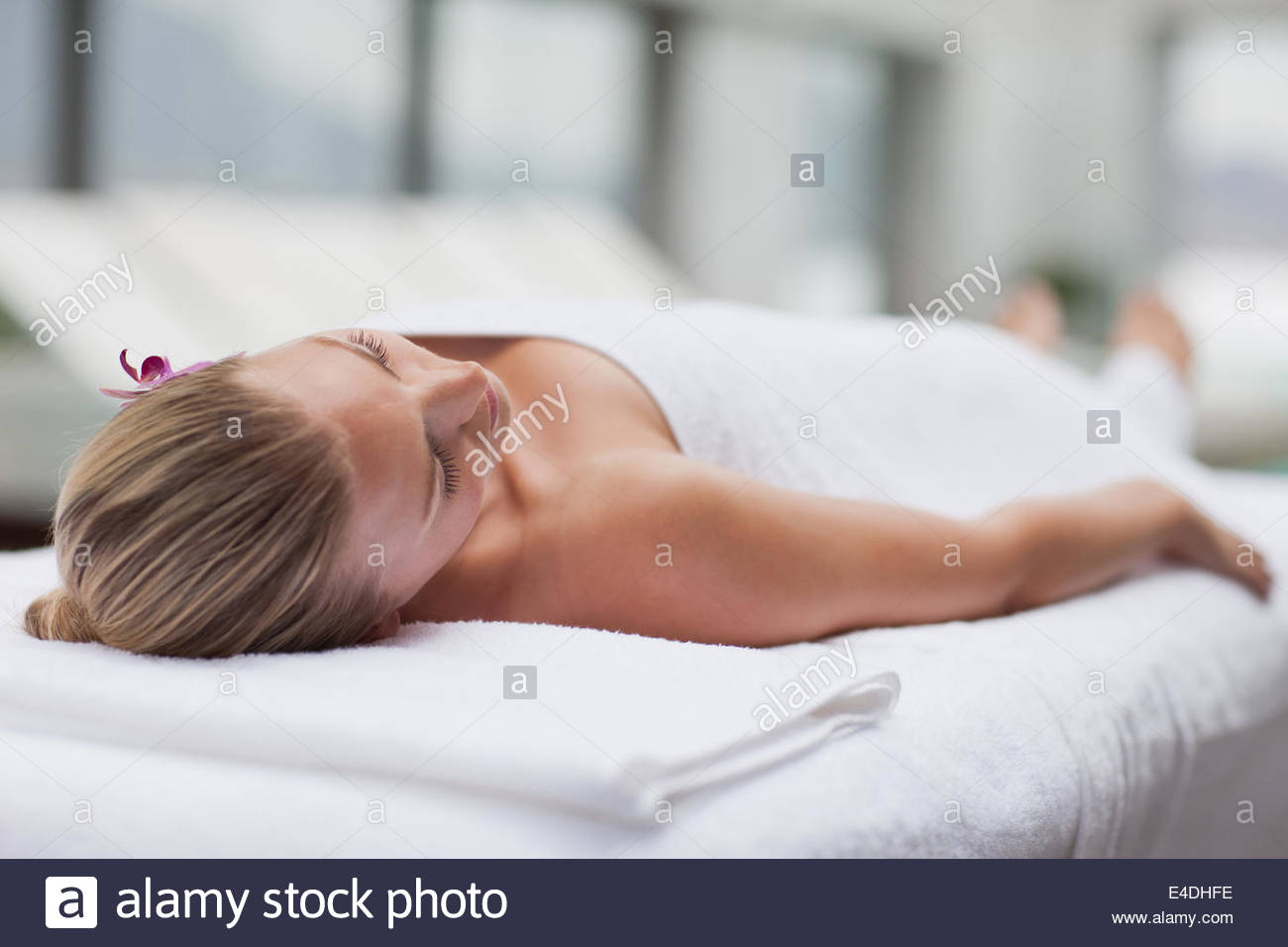 Woman laying on massage table at poolside - Stock Image