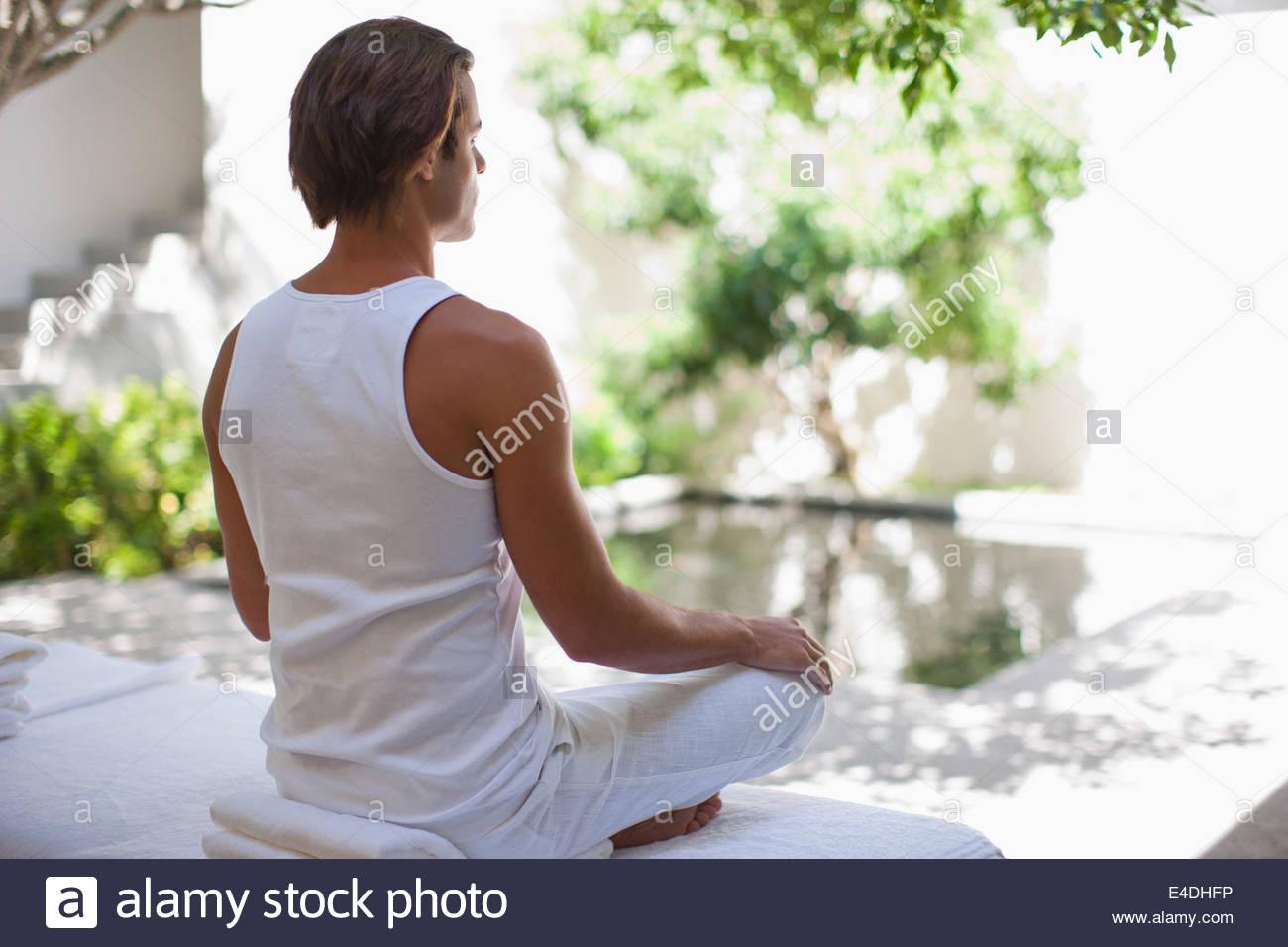 Man sitting cross-legged at poolside - Stock Image