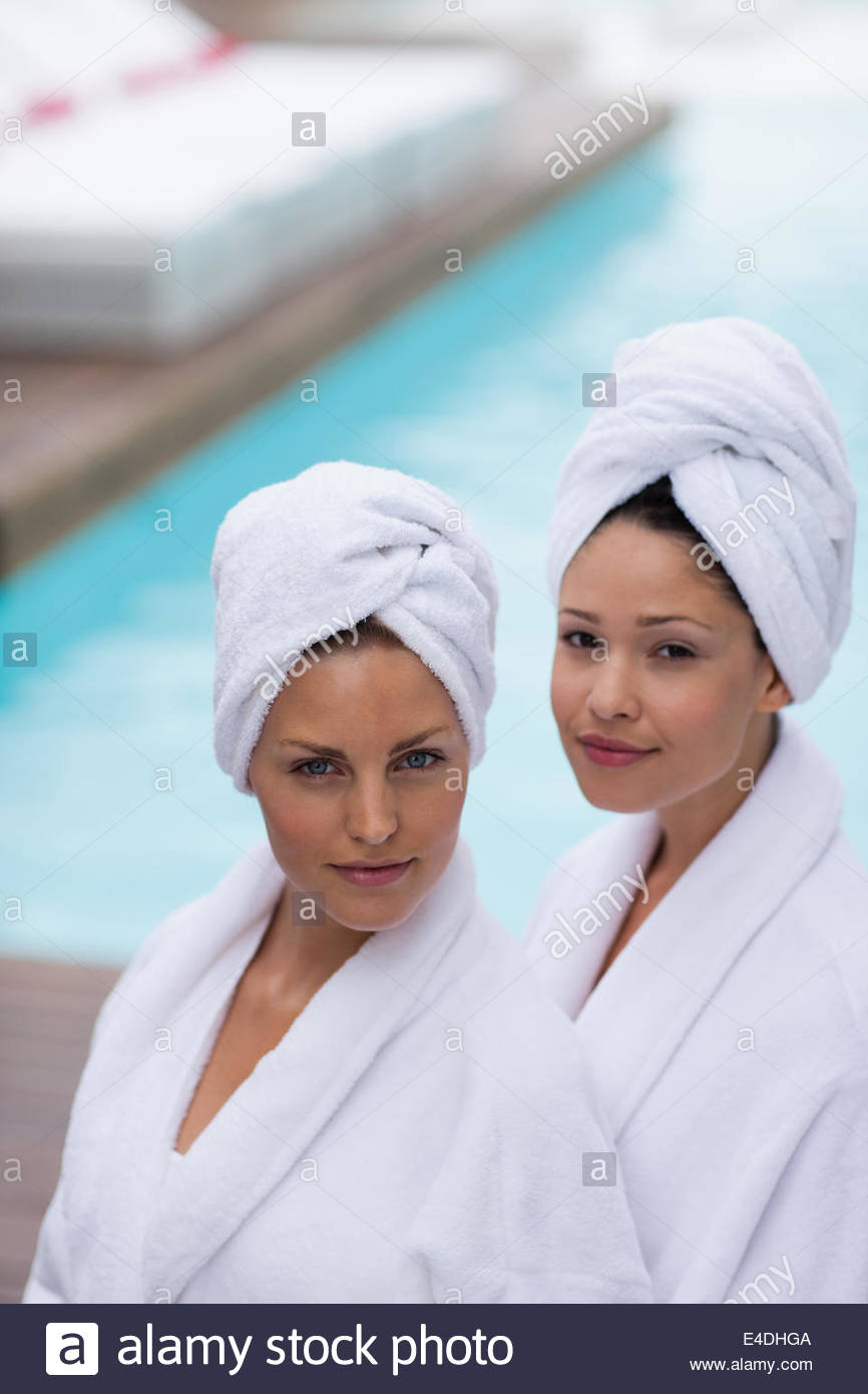 Women with hair wrapped in towels at poolside - Stock Image