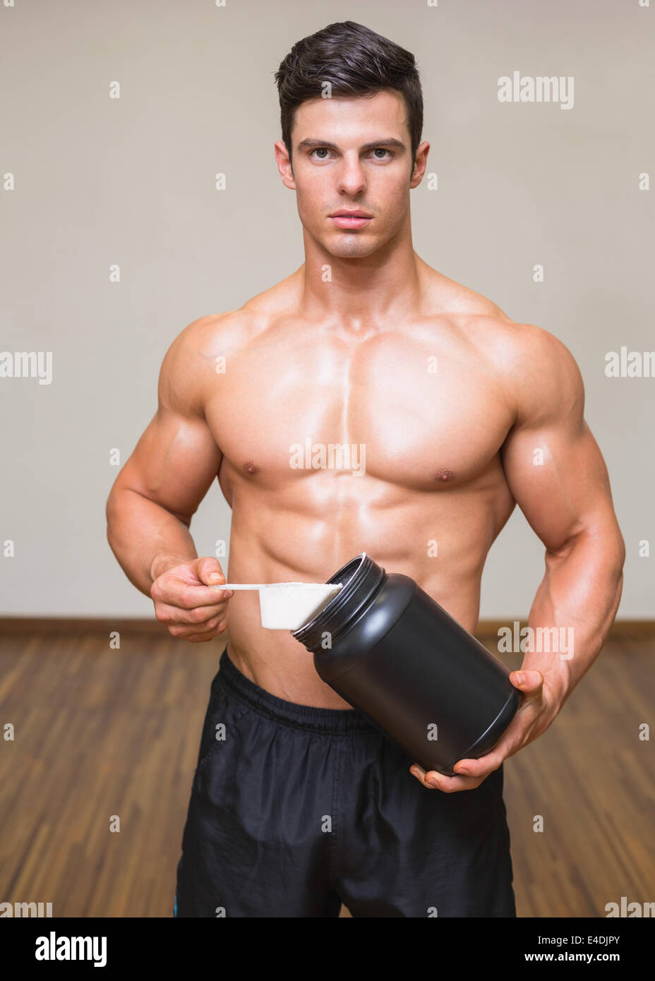 Body builder holding a scoop of protein mix in gym Stock Photo