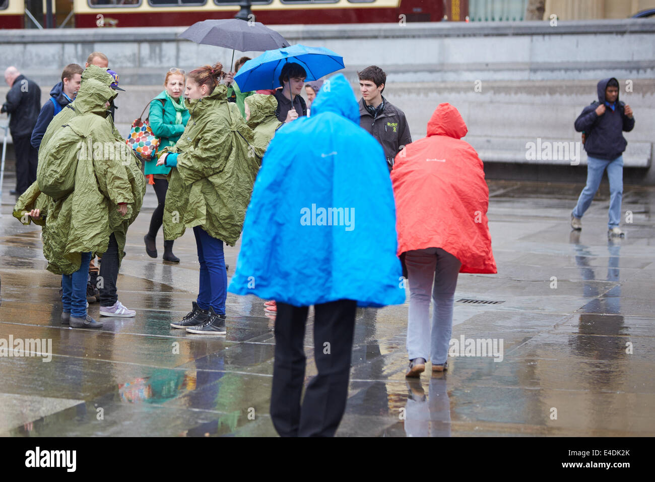 Tourists wearing ponchos to protect themselves from the rain in Trafalgar Square - Stock Image