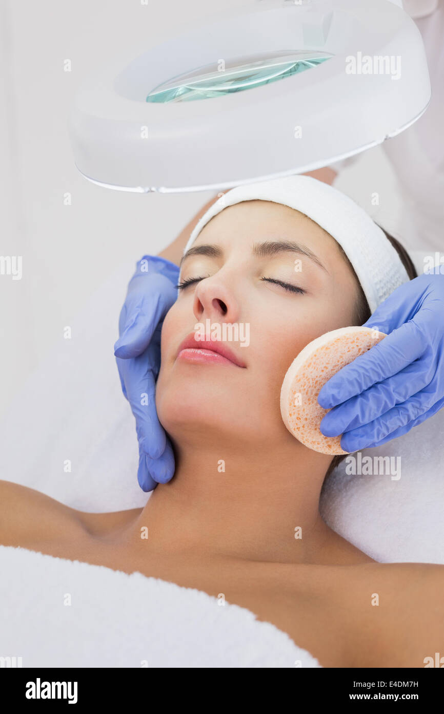 Hands cleaning woman's face with cotton swab - Stock Image