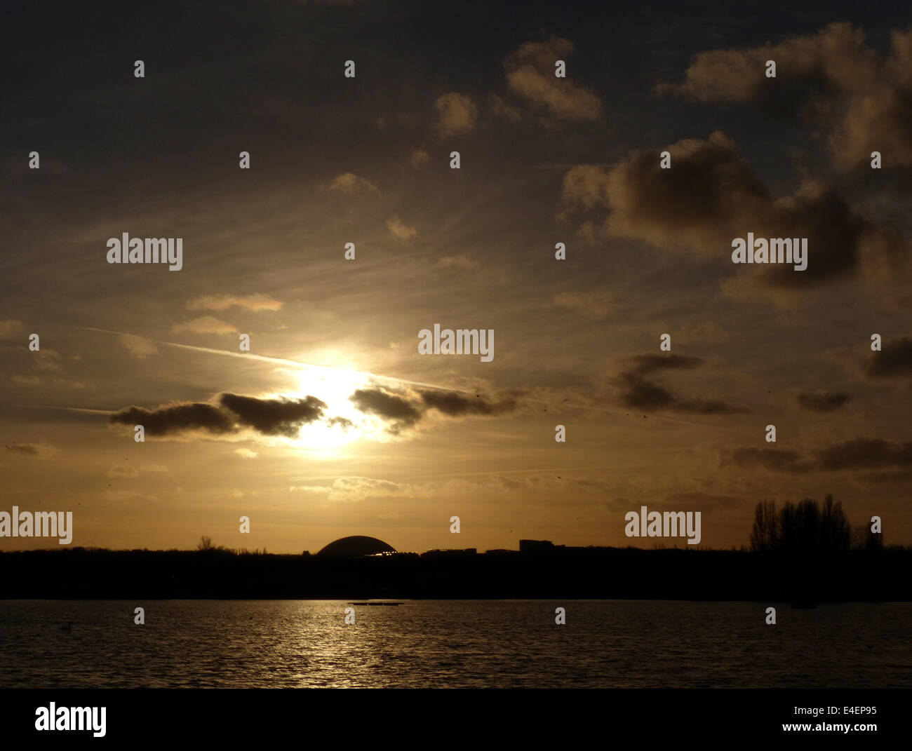 A sunset over Willen Lake in Milton Keynes with Xscape silhouetted - Stock Image