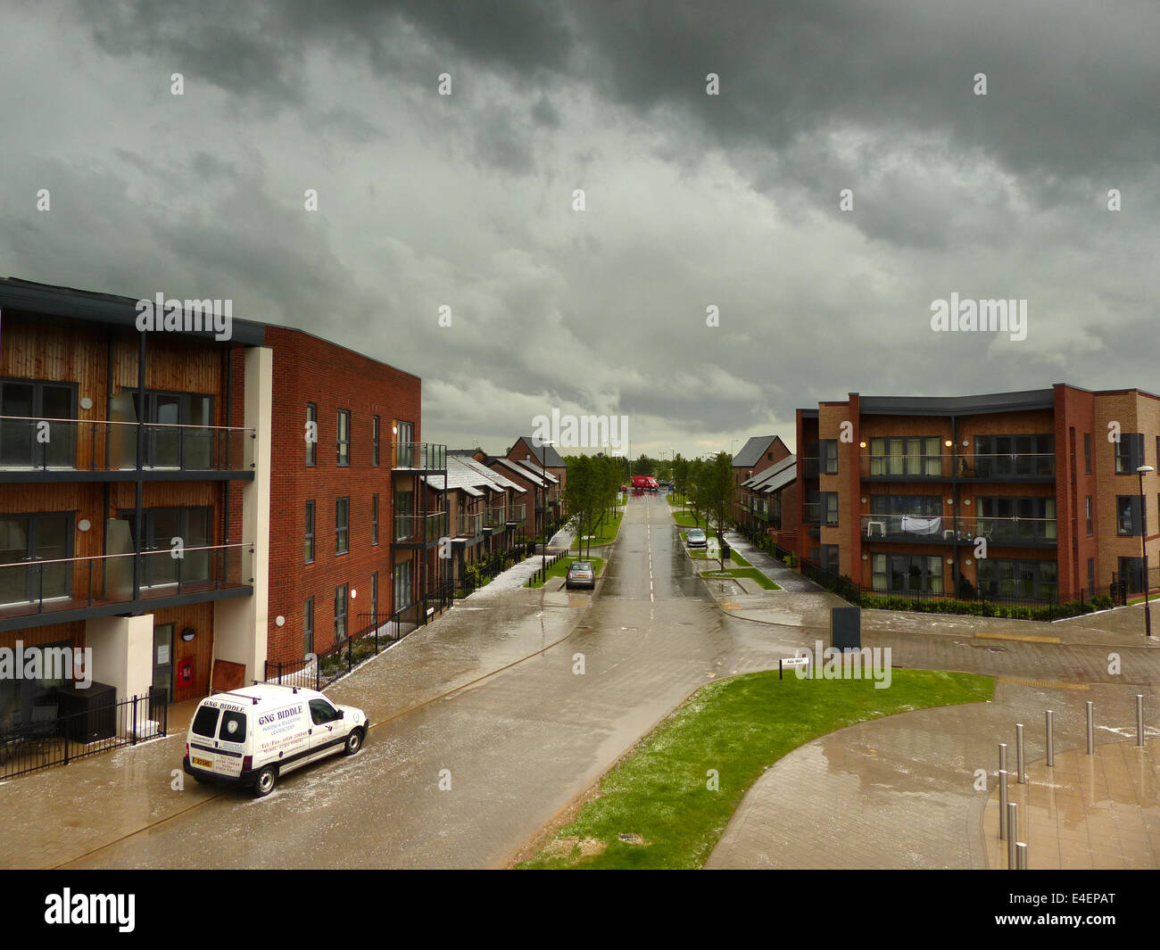 A view of a deserted housing estate during a storm with wet pavements and a very dark sky - Stock Image