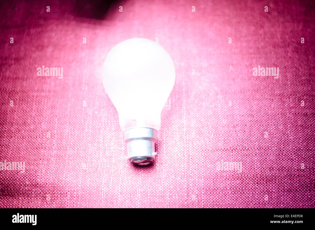 Glowing unplugged lightbulb against a pink textured background - Stock Image