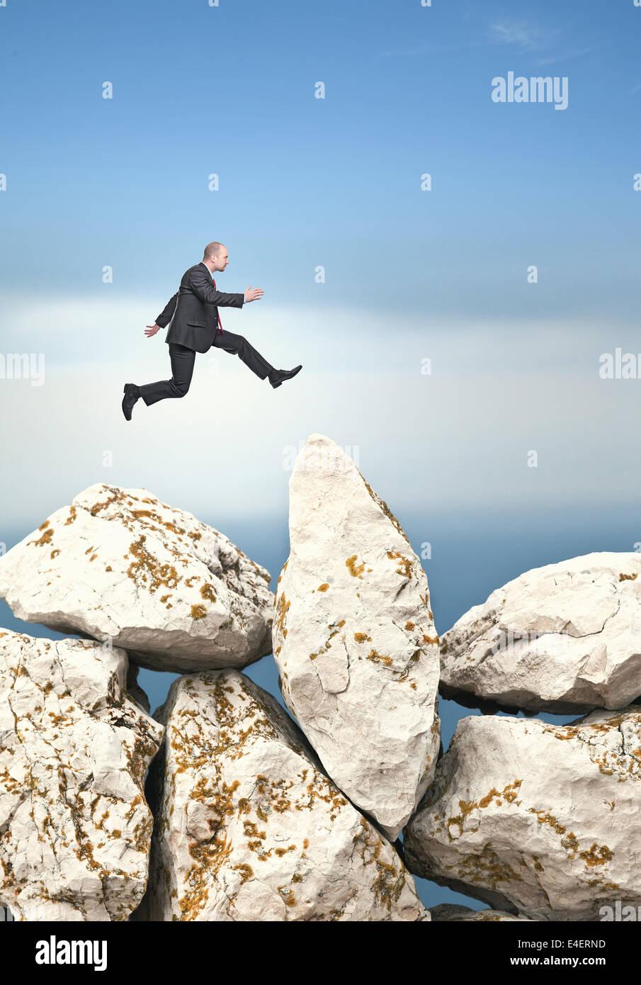 businessman jump over huge rock - Stock Image