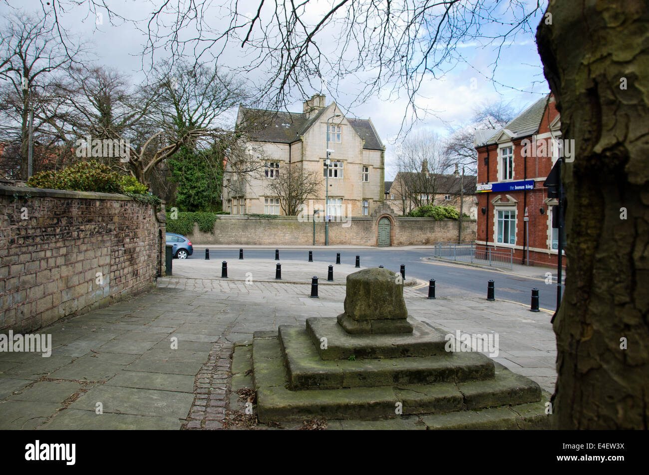 The remains of the old village cross a Scheduled Ancient Monument with Clerkson's Hall in the background - Stock Image