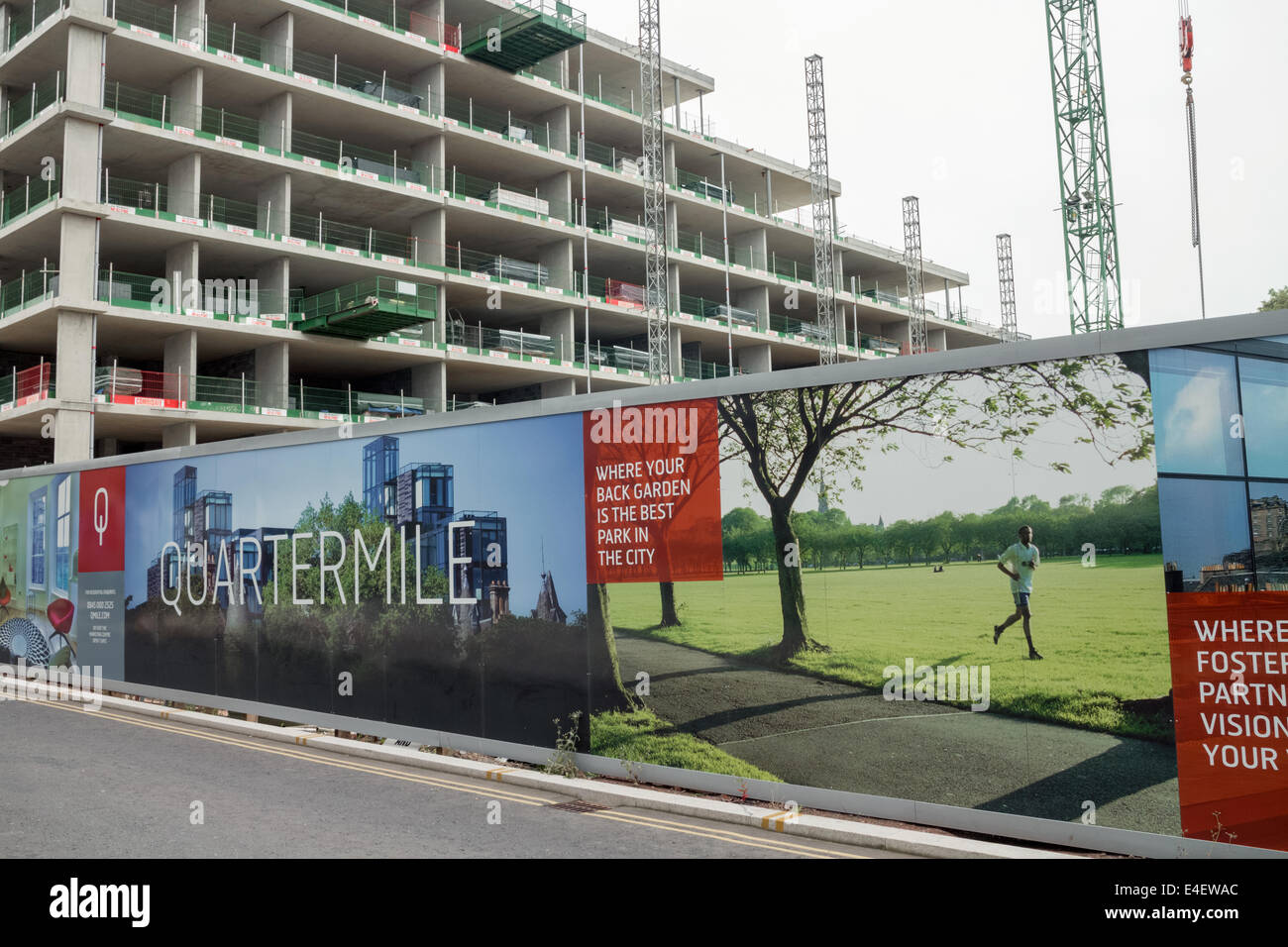 Billboard at the side of a street with a new apartment block under construction in Edinburgh's Quartermile - Stock Image