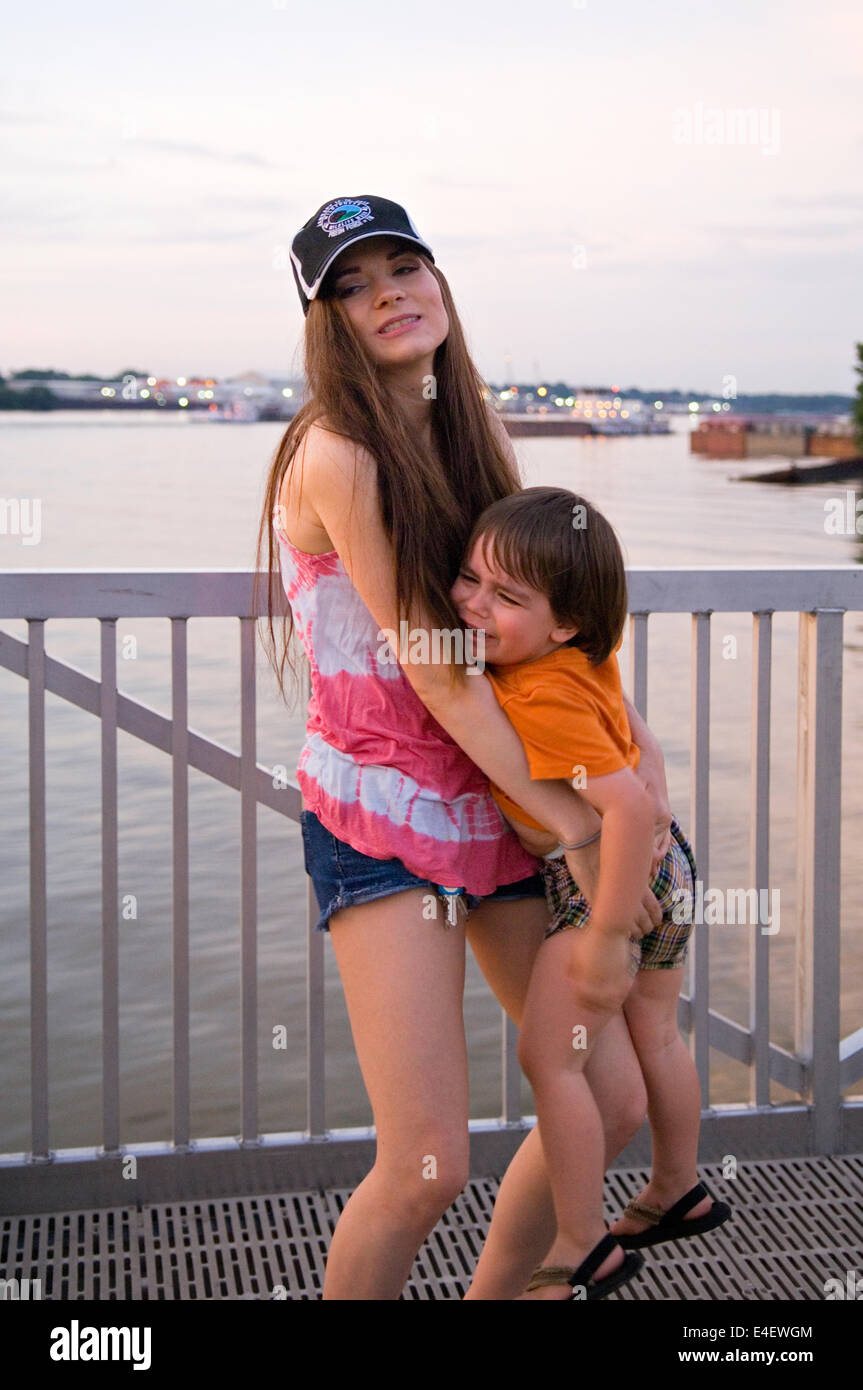 Mother Trying to Hold Upset Three Year Old Boy at Waterfeont Park in Louisville, Kentucky - Stock Image